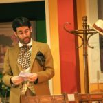 Theatre performance man with dark hair, beard, glasses, wearing clothes from the 1930s, mustard blazer. Hat holder to his left, he is reading a letter. He looks surprised.