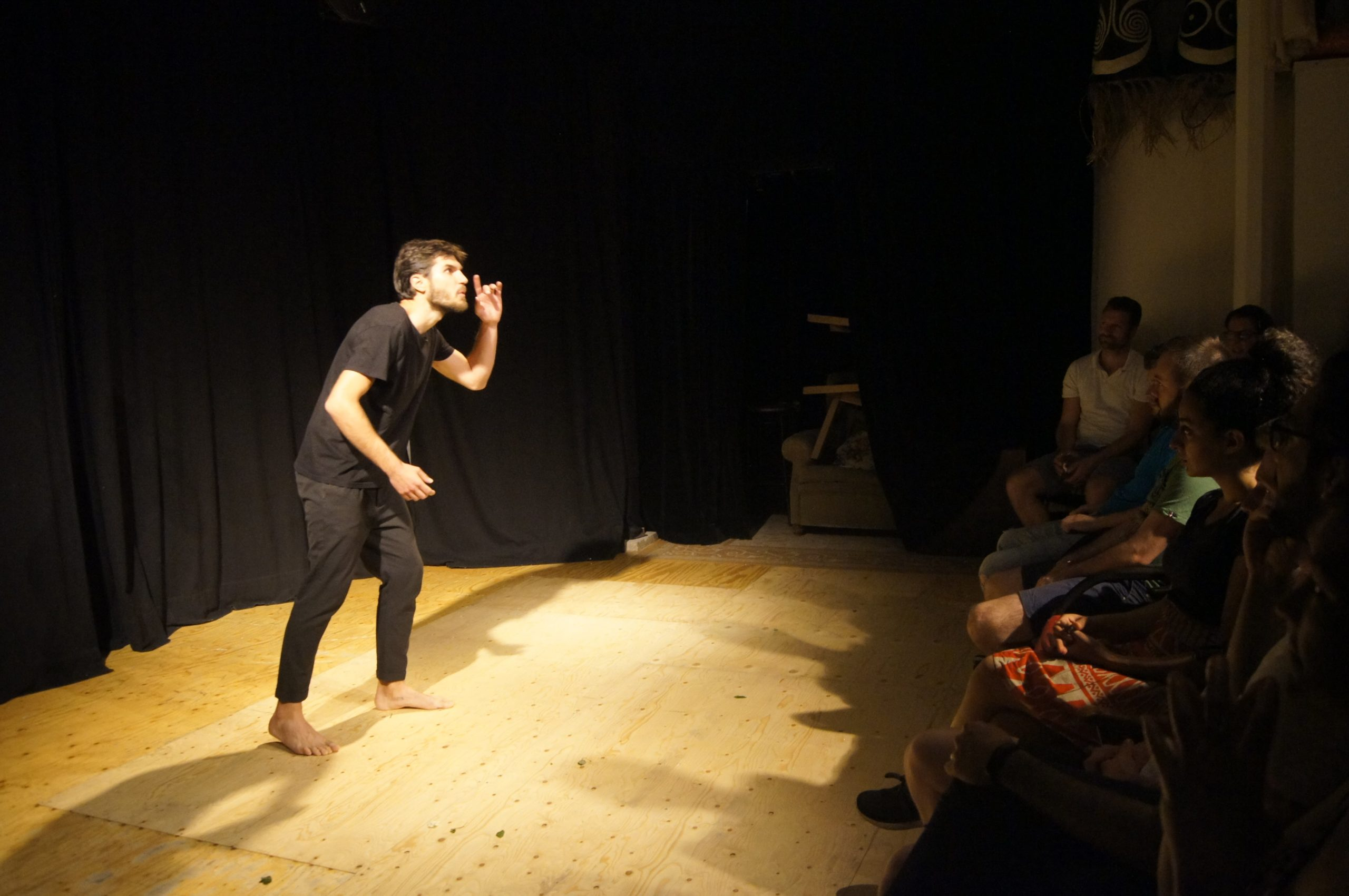 Theatre performance, man on stage with black clothes, standing in front of audience, barefoot. He acts like he hears something