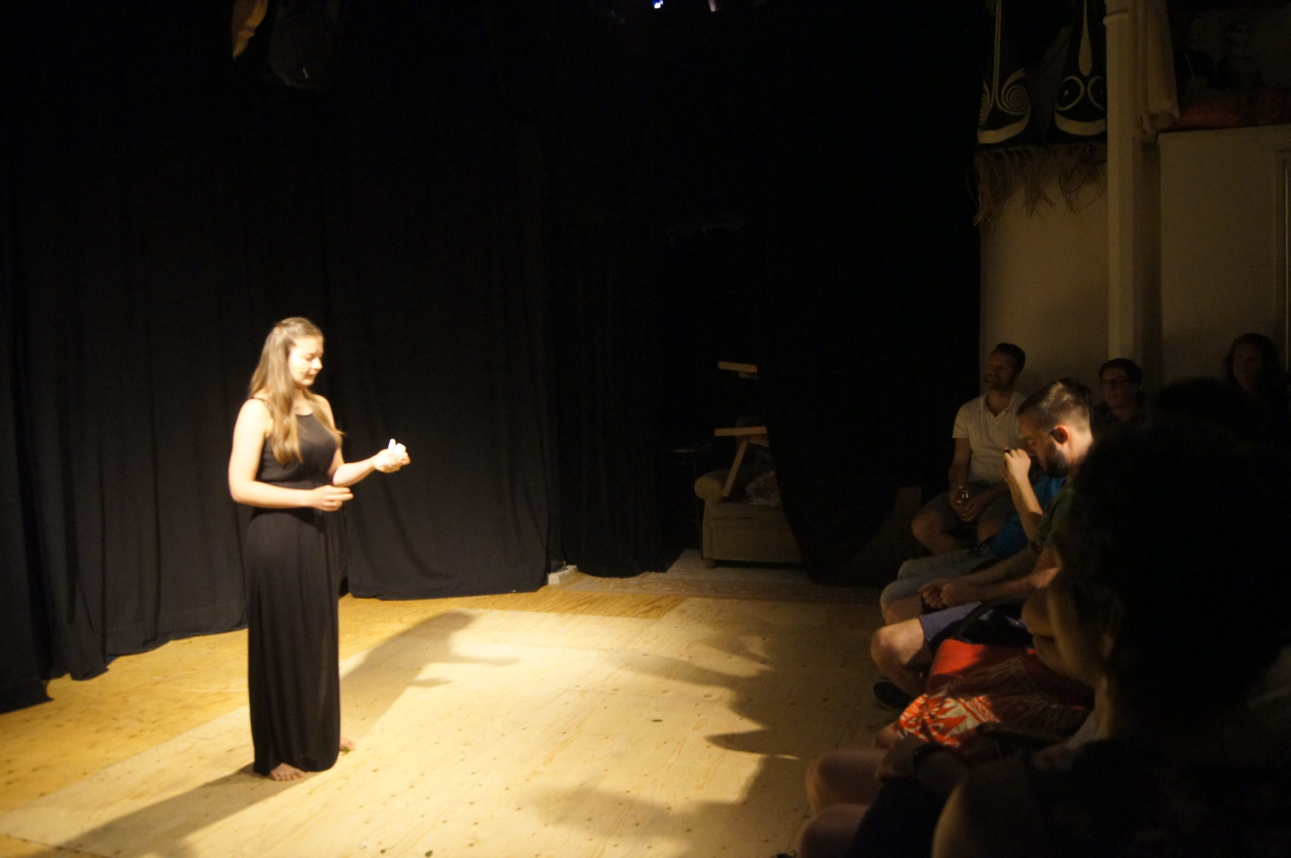 Theatre performance, woman on stage with a black dress, dark blonde hair, golden flakes on her right cheek, in front of audience. Black curtain behind her. She looks passionate