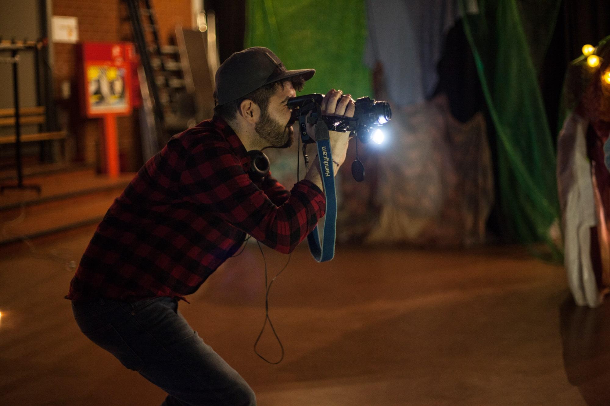 backstage man holding a camera dark hair grey baseball cap