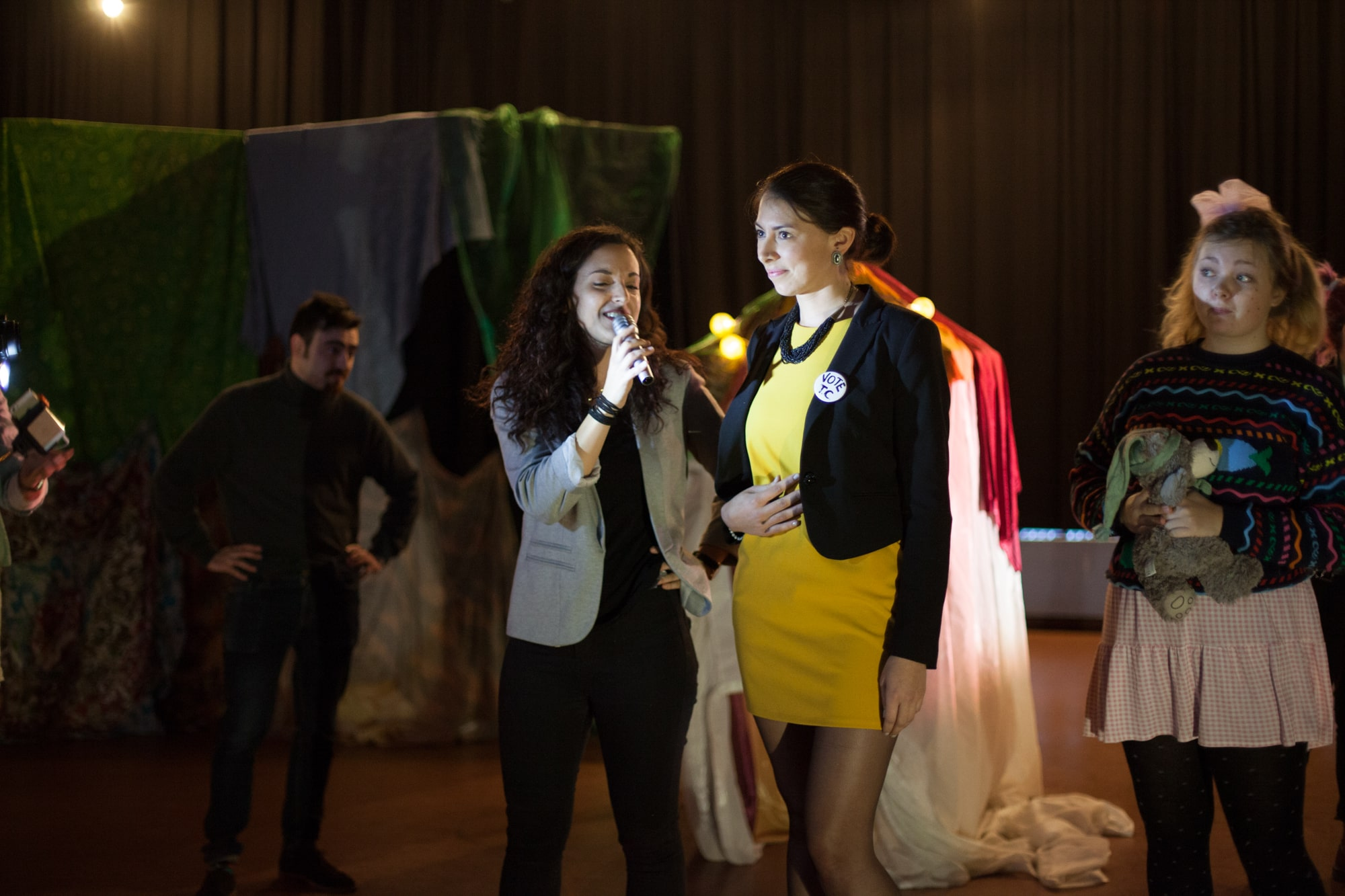 Act Attack theatre class actors performing, two women with dark hair wearing blazers. One is holding a mic interviewing the other