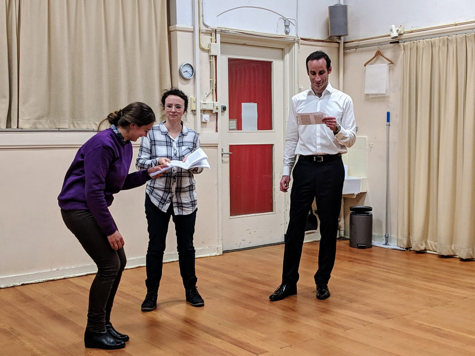 Acting Class Act Attack. Three people, two women one man, read lines. One of the women laughs.