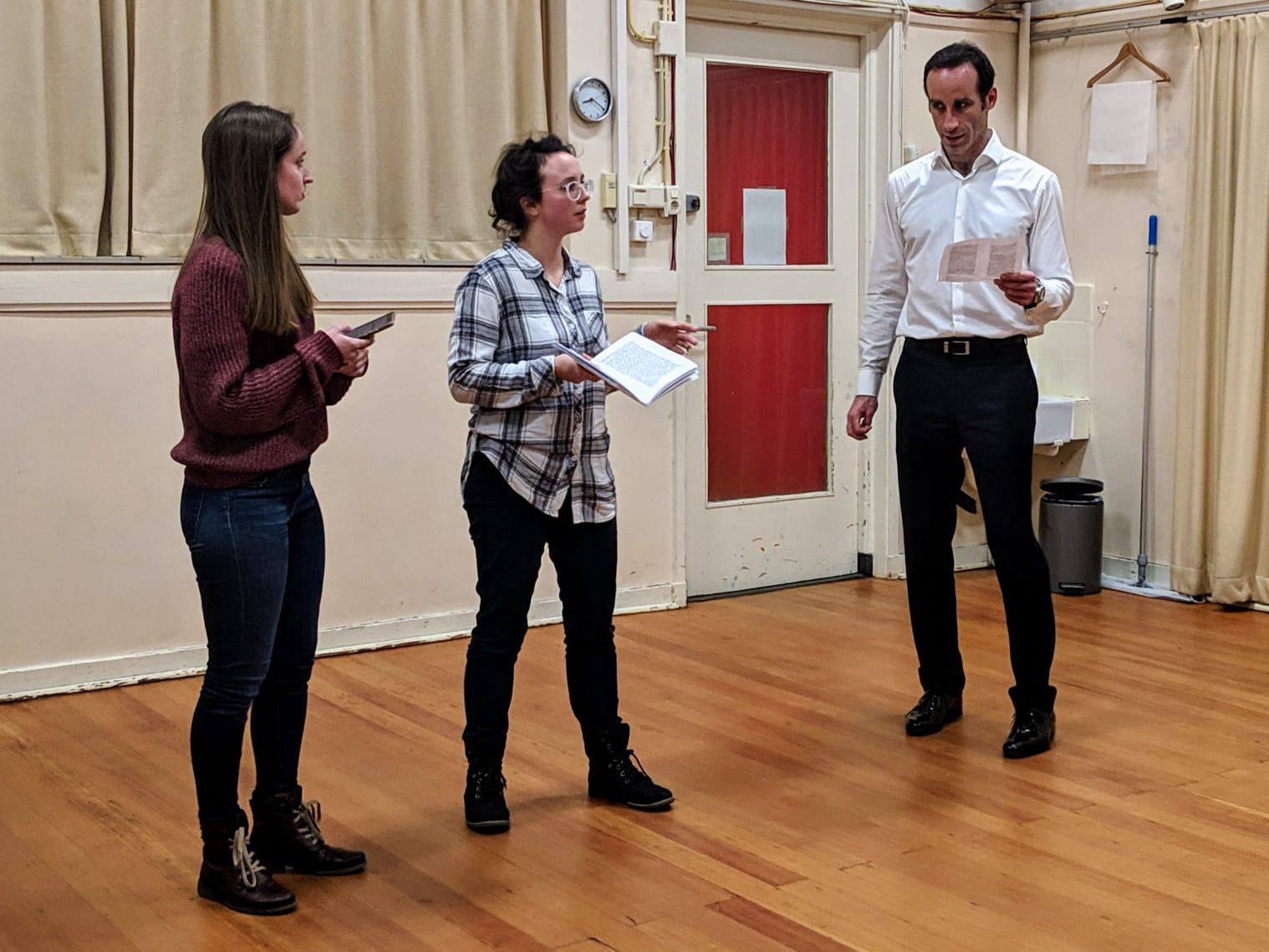 Acting Class Act Attack. Three people, two women one man, read lines. The two women look toward the man.