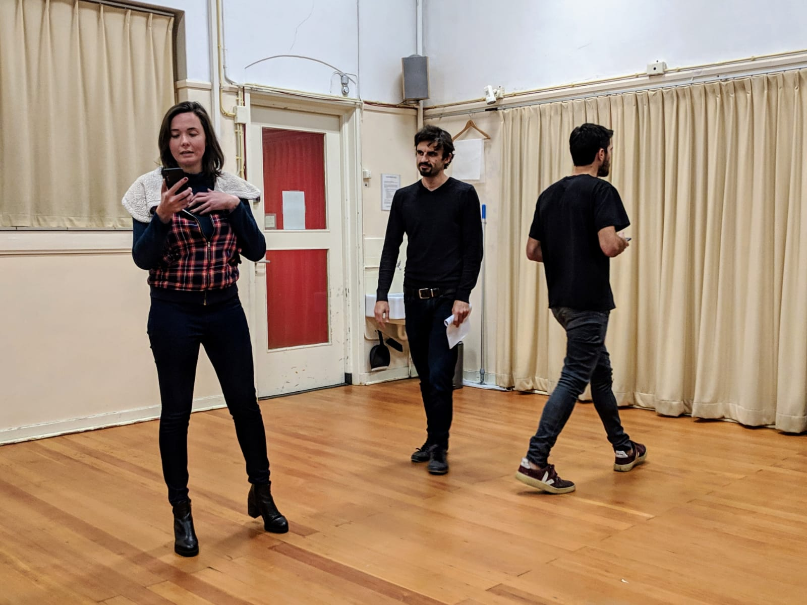 Acting Class Act Attack. Three people, two men one woman, read lines. The woman is on her phone, the two men walk up and down.