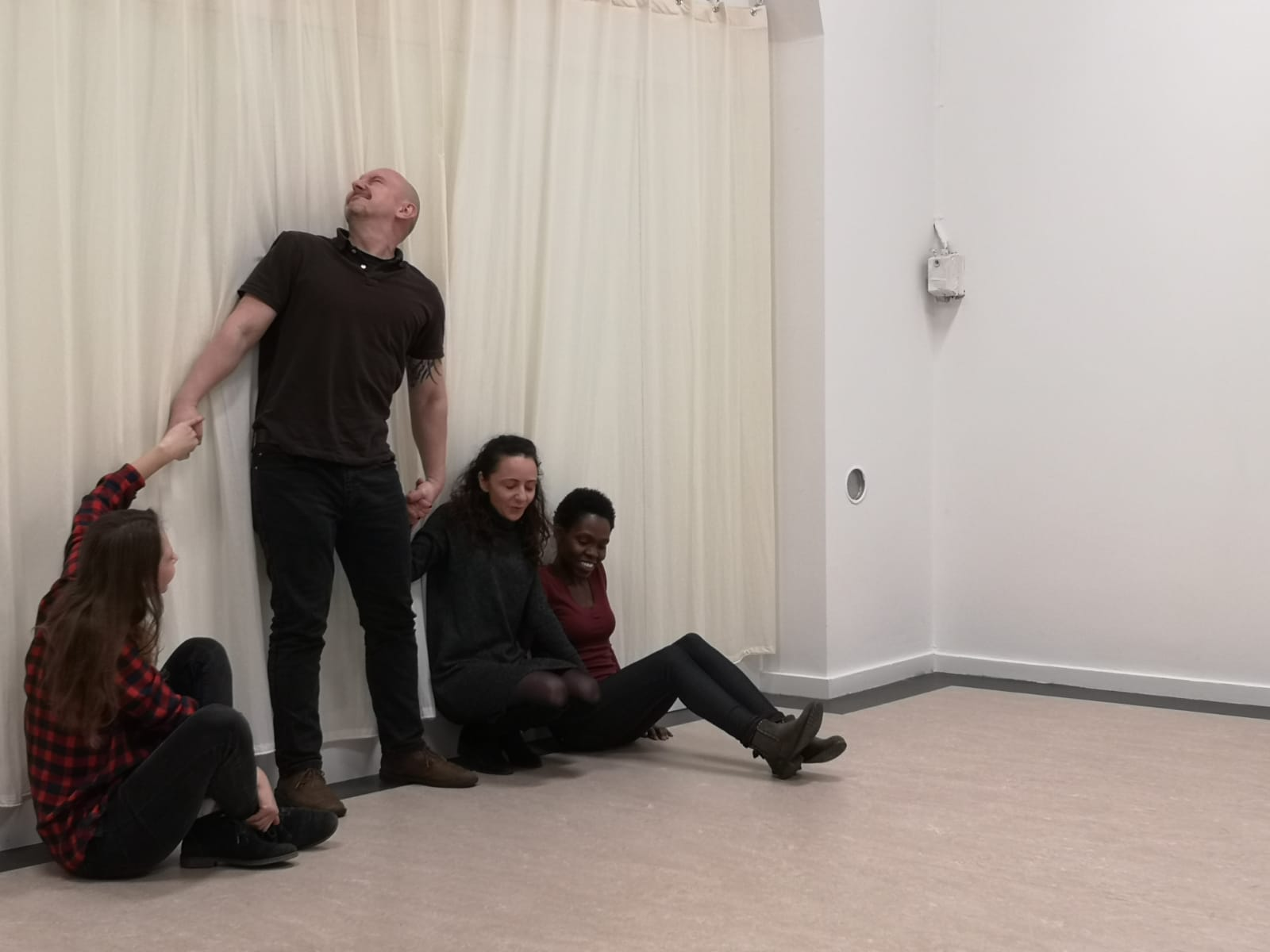 Acting Class Act Attack. Four people, three women, one man, are in a row and have their backs against the wall. The women sit on the floor. Two of them hold hands with the man who is standing