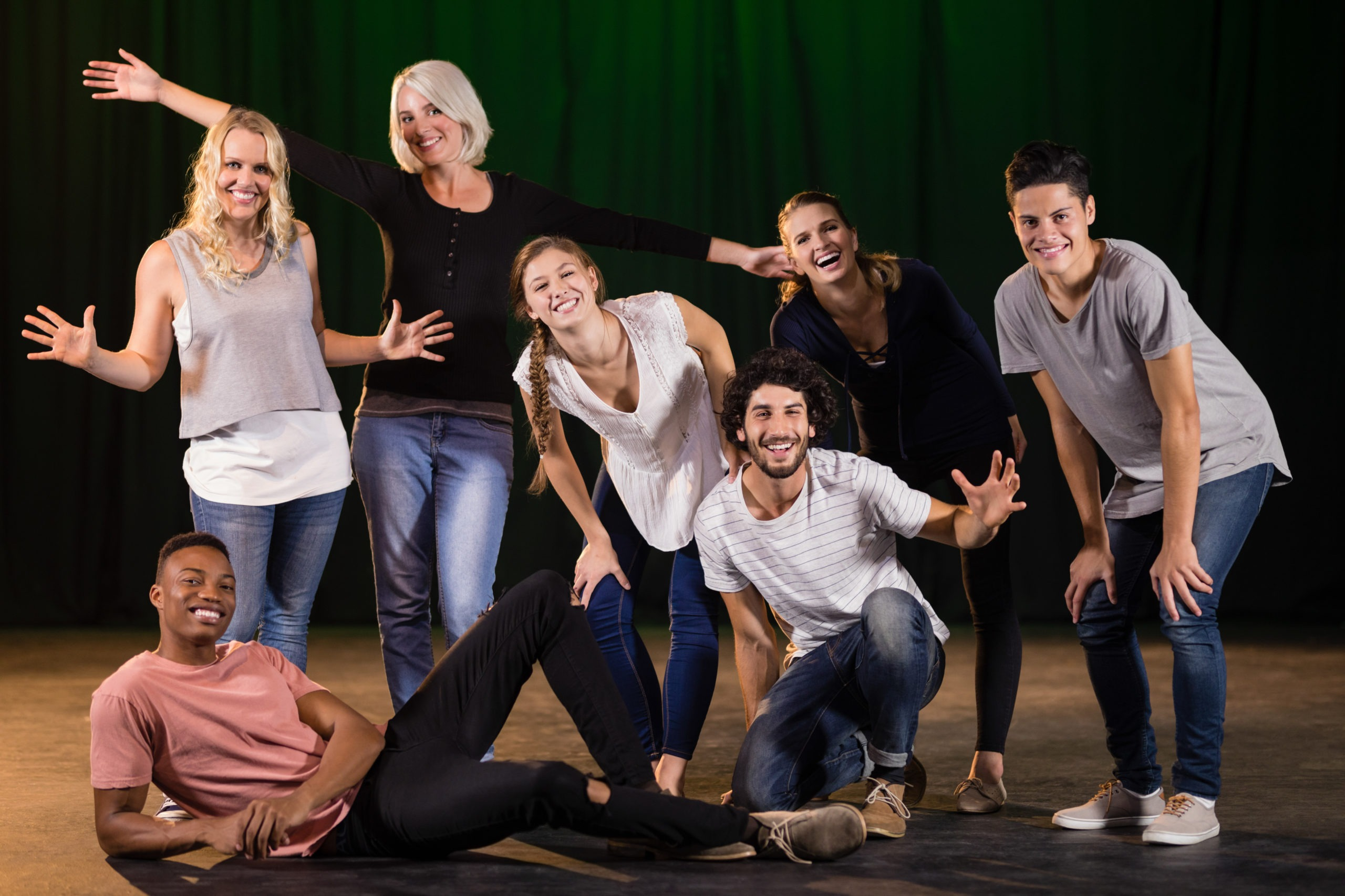 Actors practicing play on stage. A group of people are posing for a picture