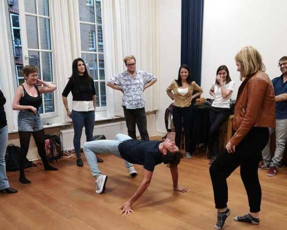 Photo from Improv and Physical class. One man is doing a bridge pose while a group watches him, forming a semi-circle.