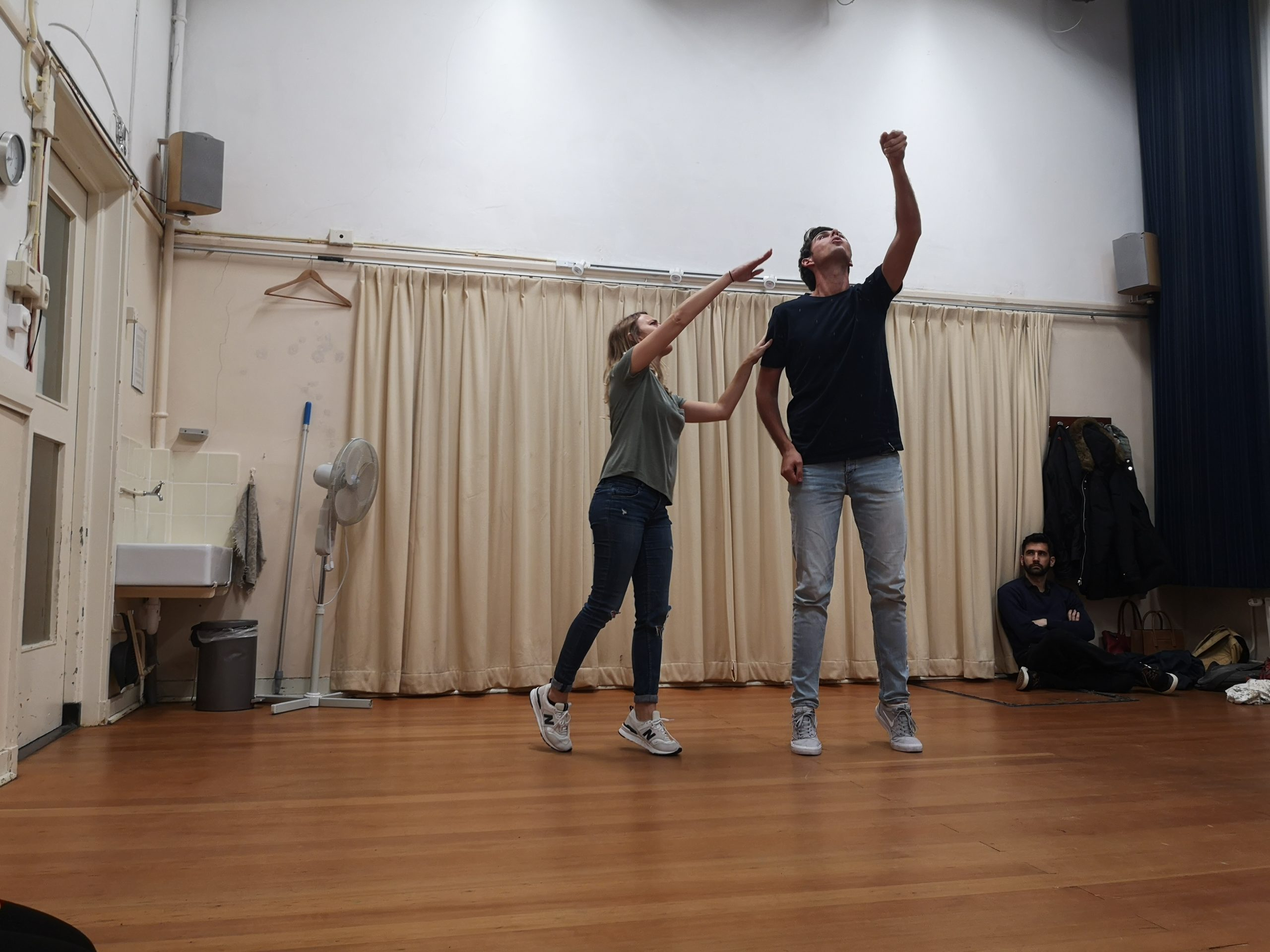 Improv and physical. A man reaches his arm up like he's holding something. A woman is standing next to him, also reaching her arm, pointing at the imaginary object he's holding.