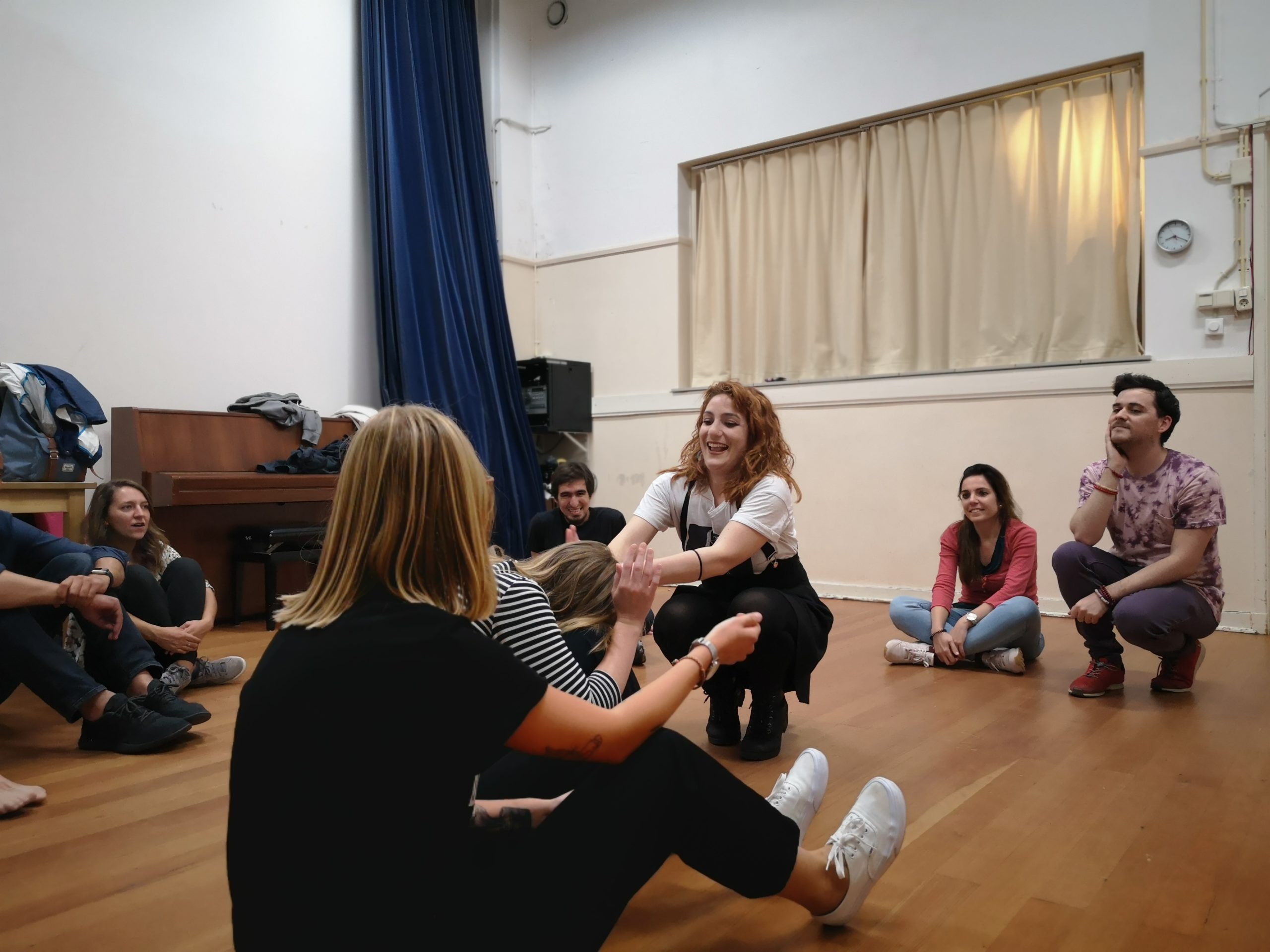 From the improv and physical class. A group sits in a circle. Three women are in the middle, two sitting, one kneeling and laughing, reaching her hands to one of the others.