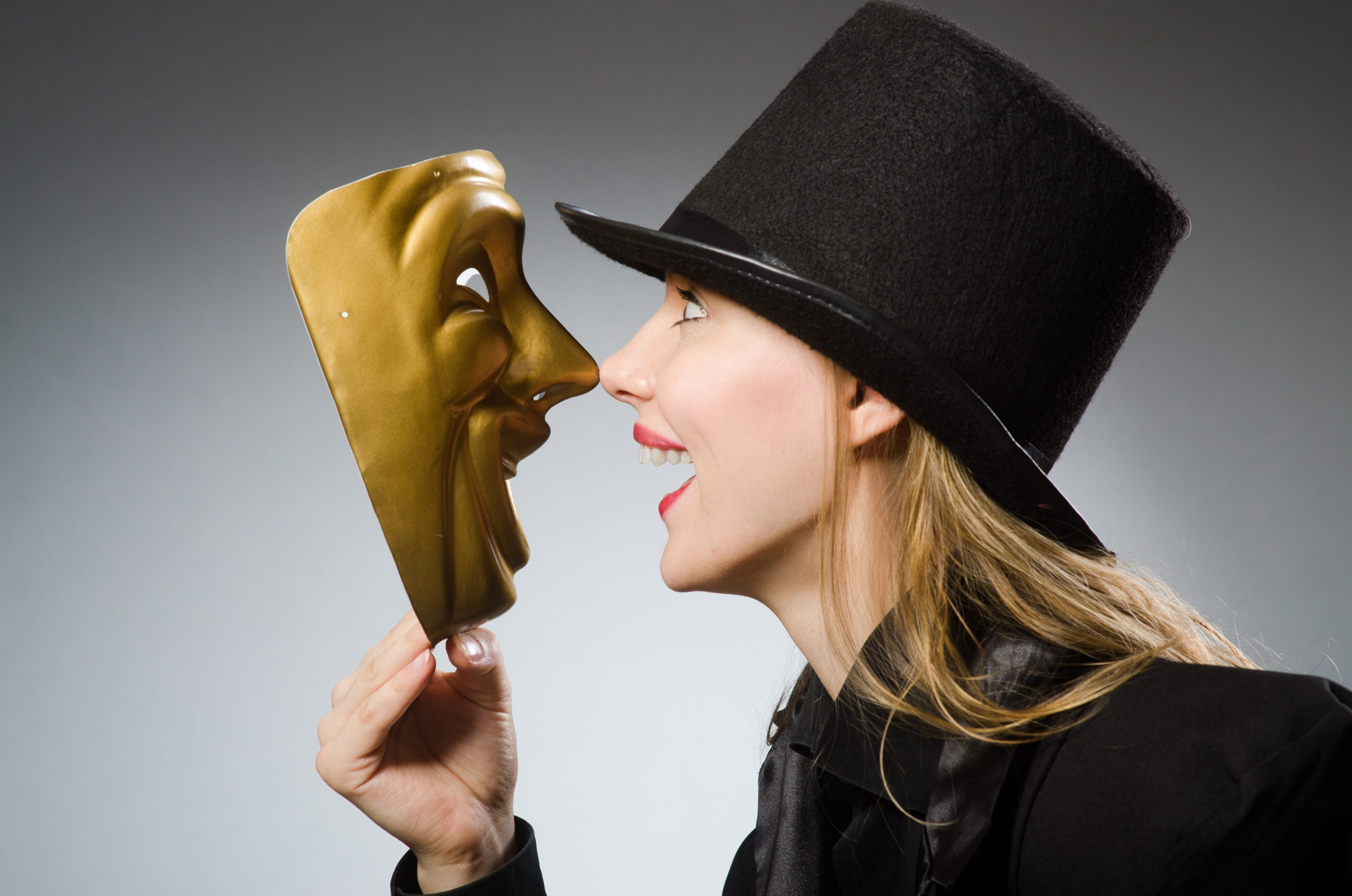 A white blond woman wearing a black top hat, smiling. She holds a golden theatre mask which also smiles