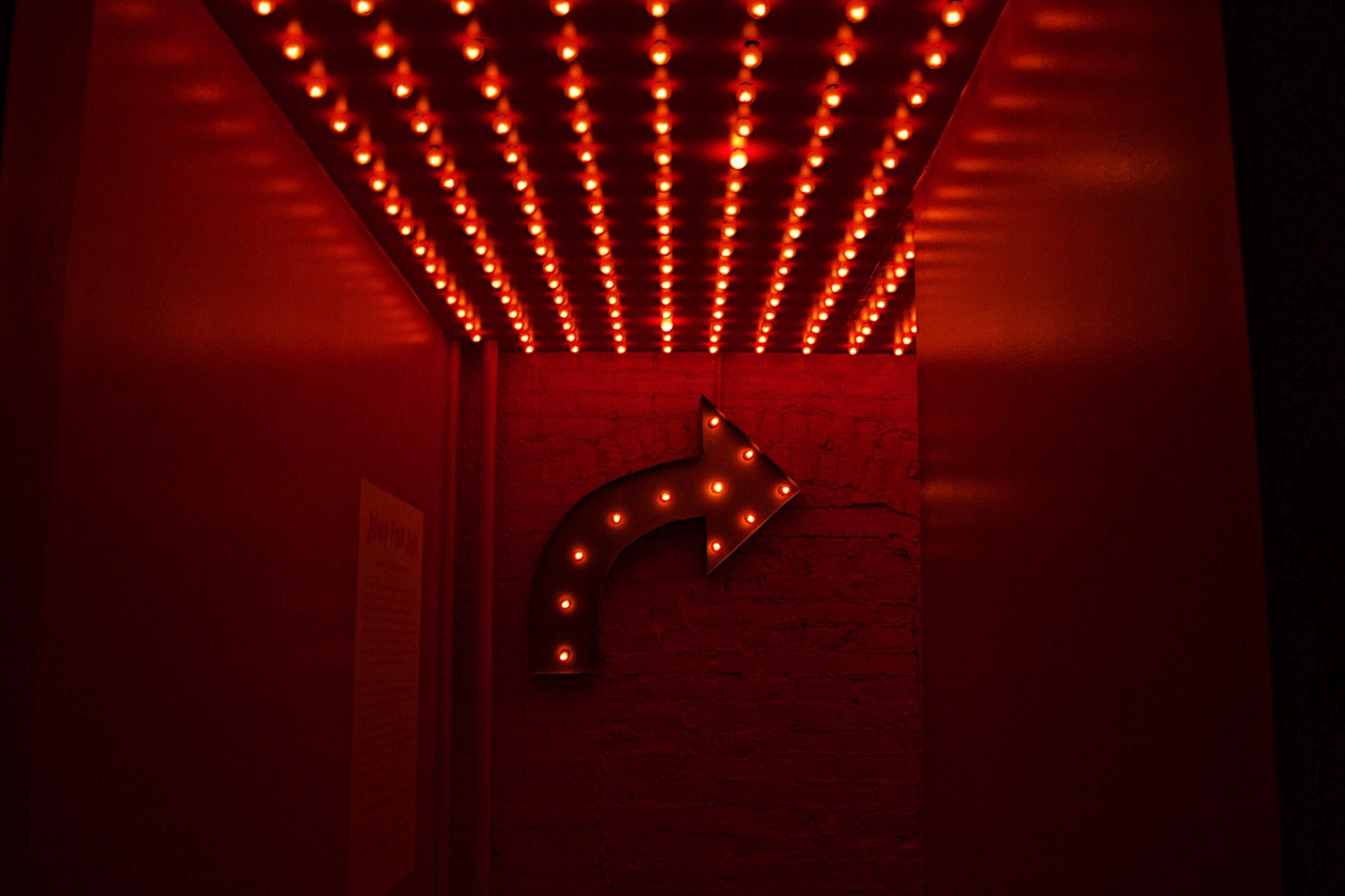 red photo. A series of light bulbs for, the shape of an arrow pointing right. A series of red lightbulbs are placed on the ceiling as well.