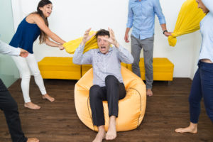 Improv exercise. Four playful business people beating their friend with pillows. He is sitting on beanbag and pretending to be scared.