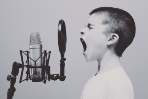 black and white photo of a five year old boy screaming or singing on a studio microphone