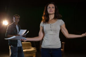 Actors rehearsing on stage. A man and a woman holding papers, reading lines. The woman looks a little agitated