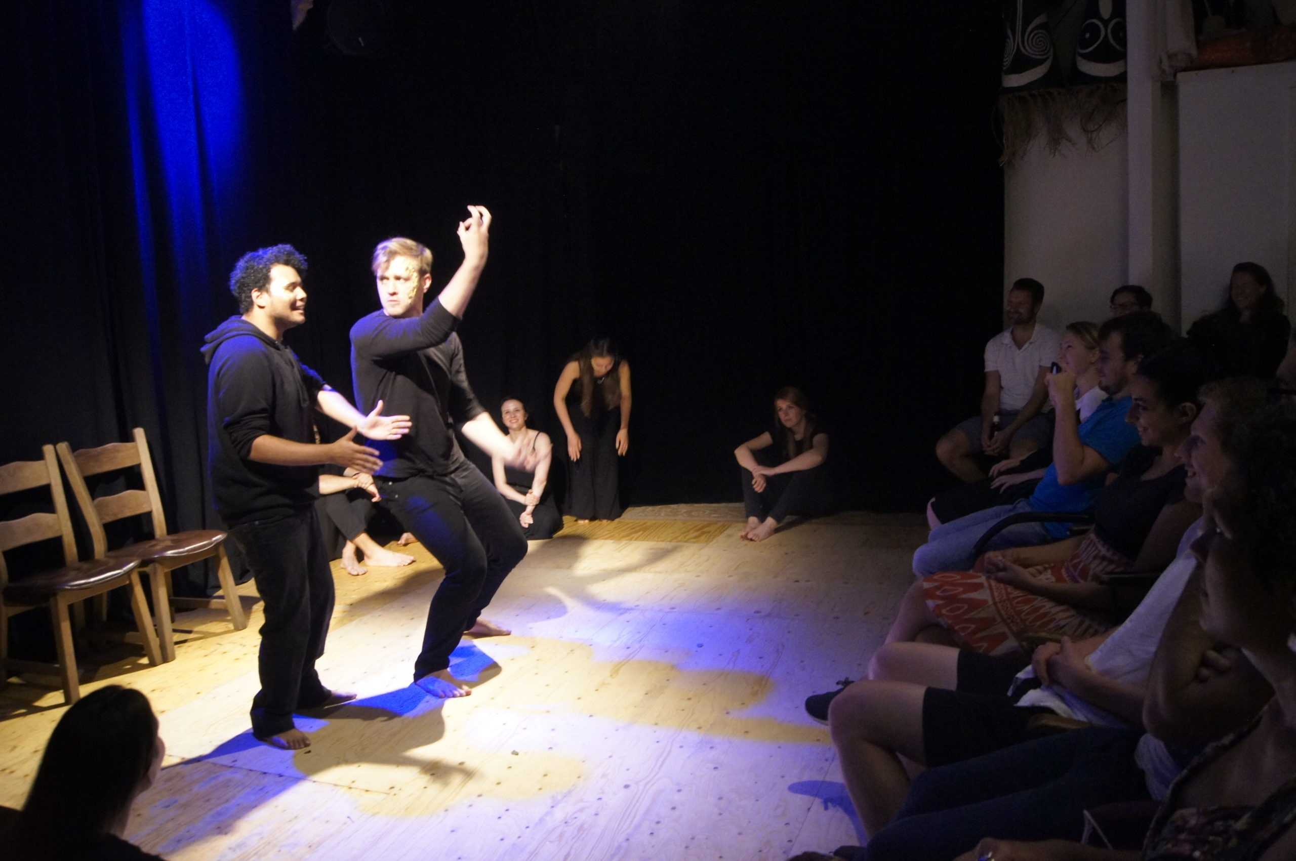 Photo from the theatre performance Keeping up with the Greeks. On the left of the photo, two male actors on stage, standing, wearing black clothes, making gestures like they're dancing. On the right, the audience.
