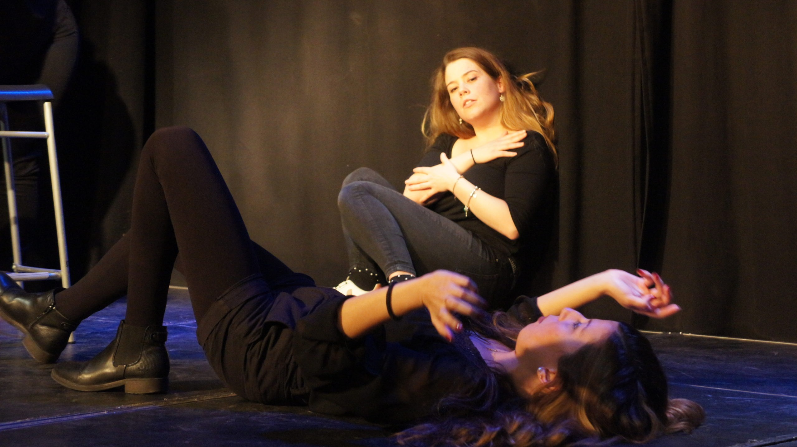Act Attack's improv and physical show. Two girls on stage wearing black. One is laying on the floor, the other is sitting against a wall.