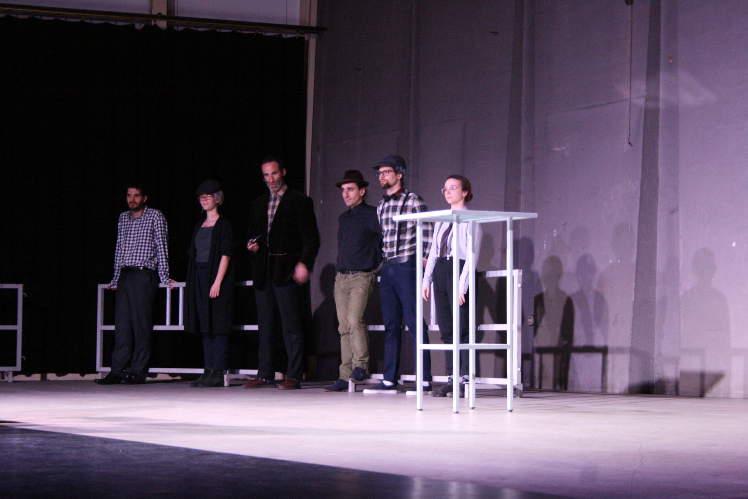 """Photo from the show """"The Chairs"""". Six actors stand on stage, wearing old-fashioned clothes, like blue plaid shirts and caps."""