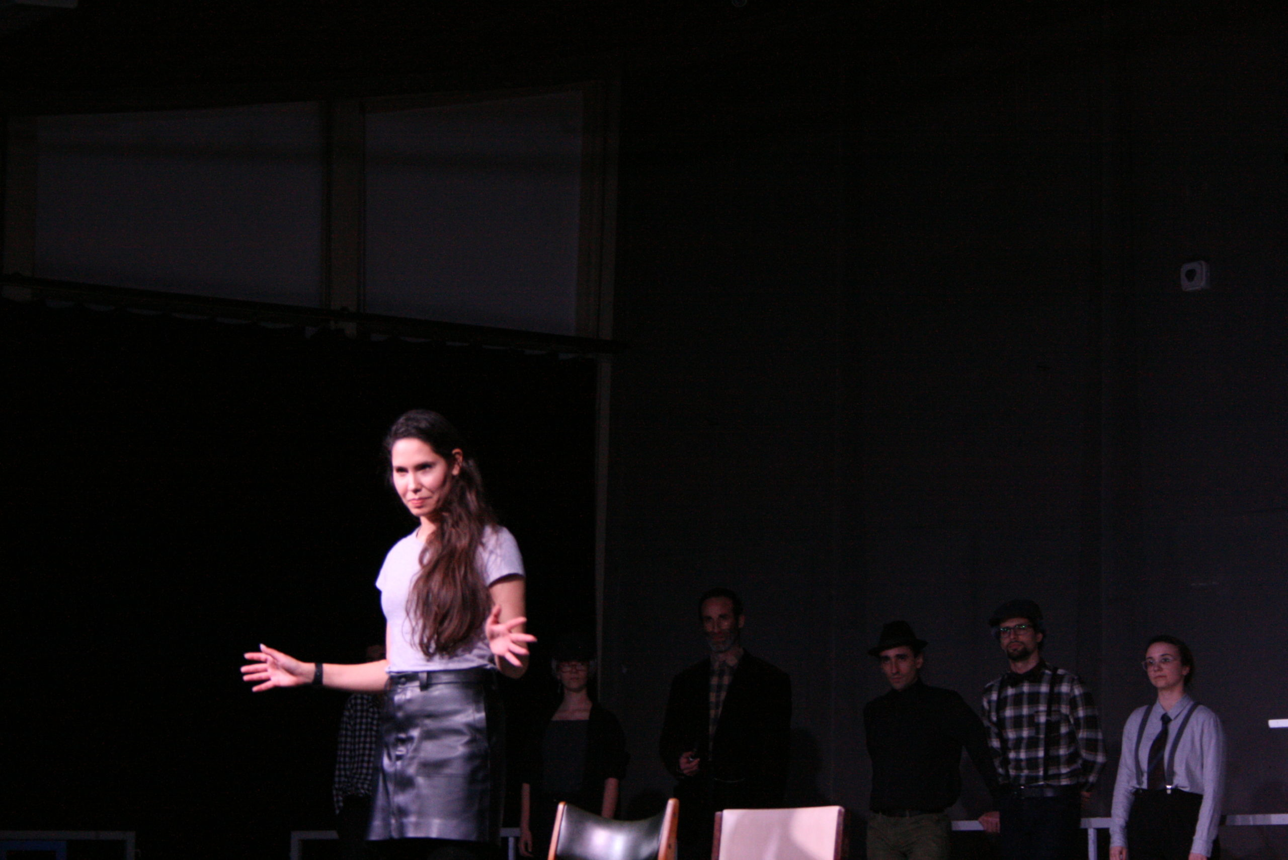 """Photo from the show """"The Chairs"""". Six actors stand at the back of the stage, wearing old-fashioned clothes, like blue plaid shirts and caps. A female actor stands at the front, doing jazz hands"""