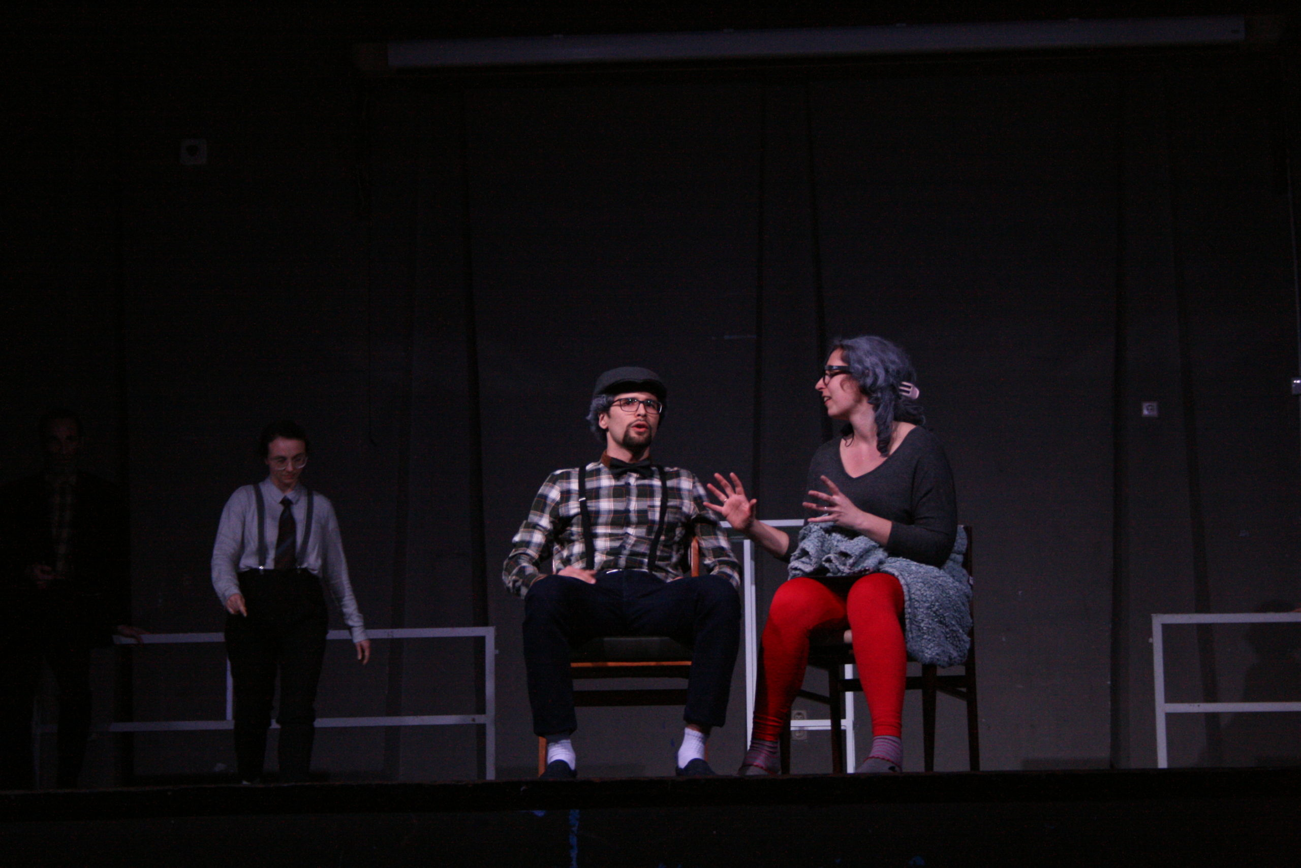 """Photo from the show """"The Chairs"""". A male and a female actor sit on chairs, talking. He looks over the audience and she looks at him, her arms open like holding a ball"""