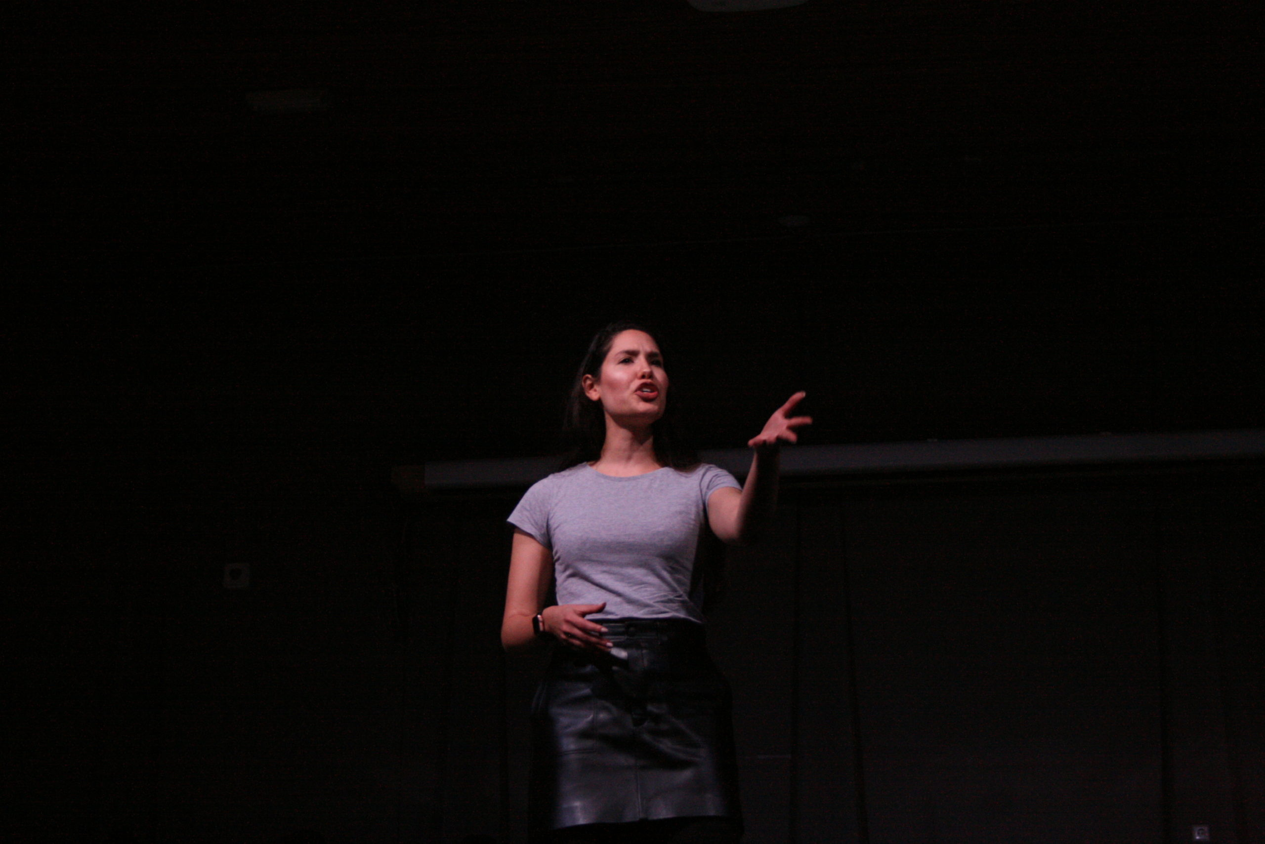 """Photo from the show """"The Chairs"""". A female actor addresses the audience. She looks angry, reaching out one of her arms."""