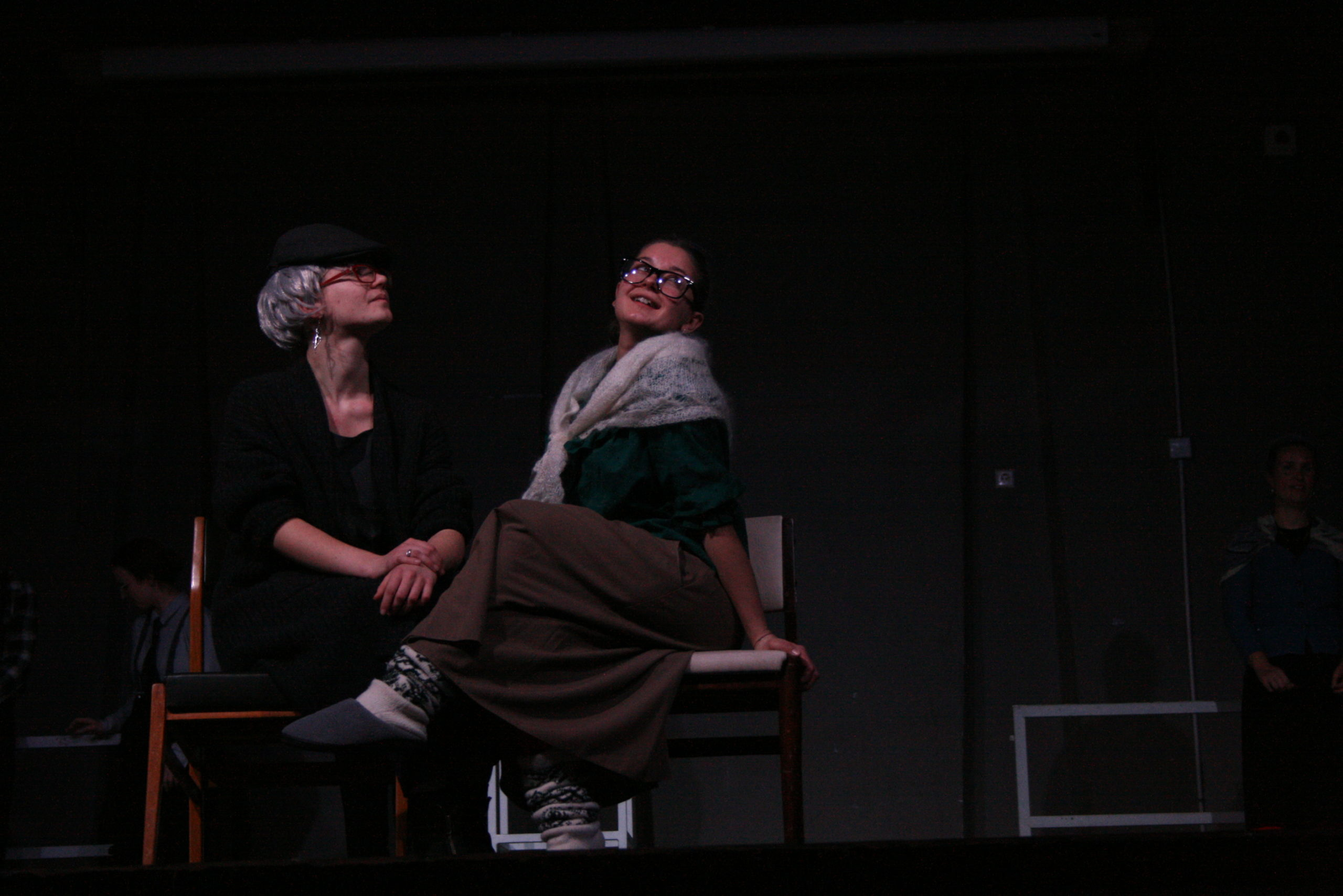 """Photo from the show """"The Chairs"""". Two female actor sit on chairs, dressed like old ladies. One of them looks flirty or happily nostalgic"""