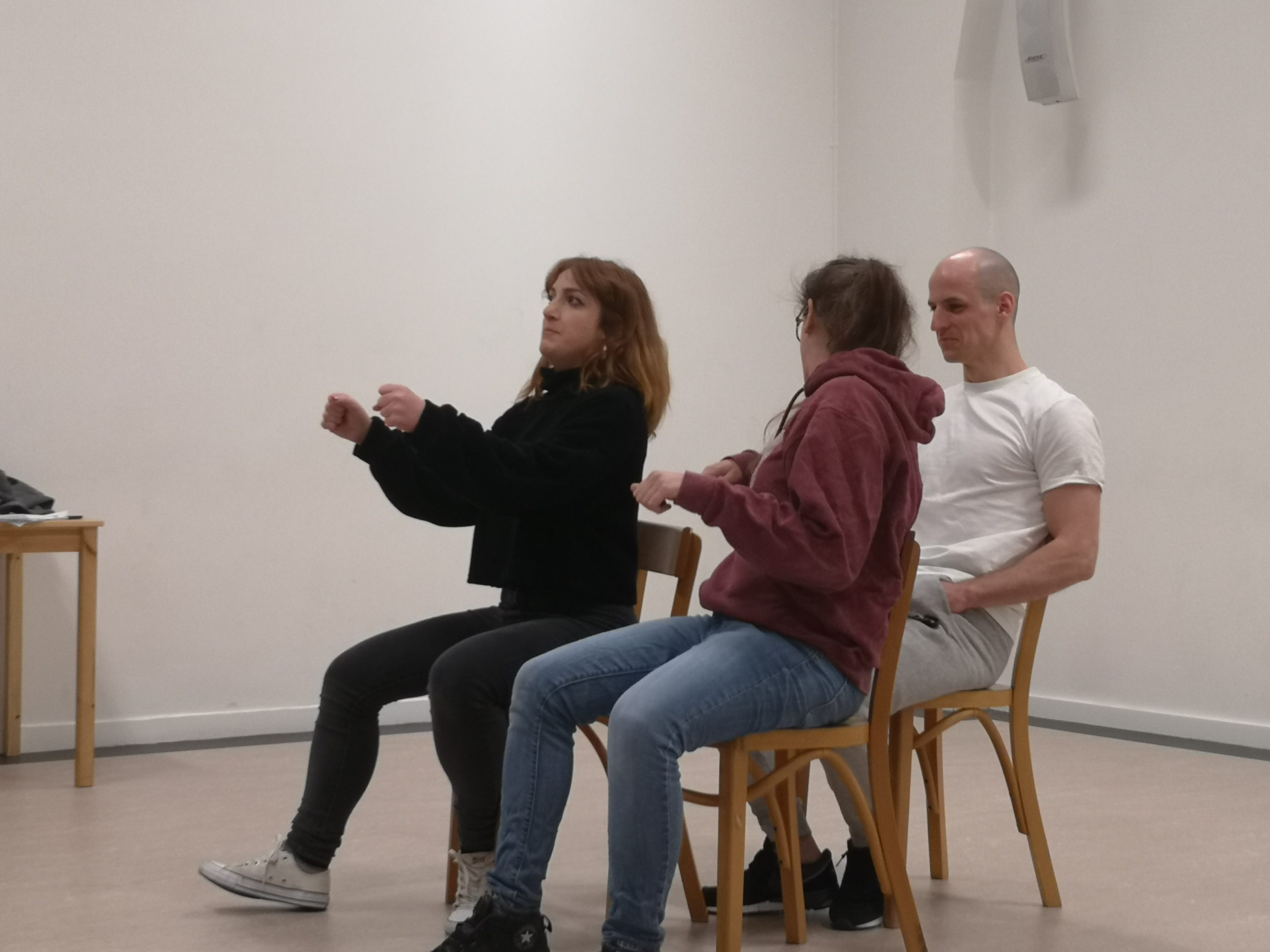 Acting class Act Attack. Three people are sitting on chairs, two at the front one at the back. The front right person, a girl, pretends to drive