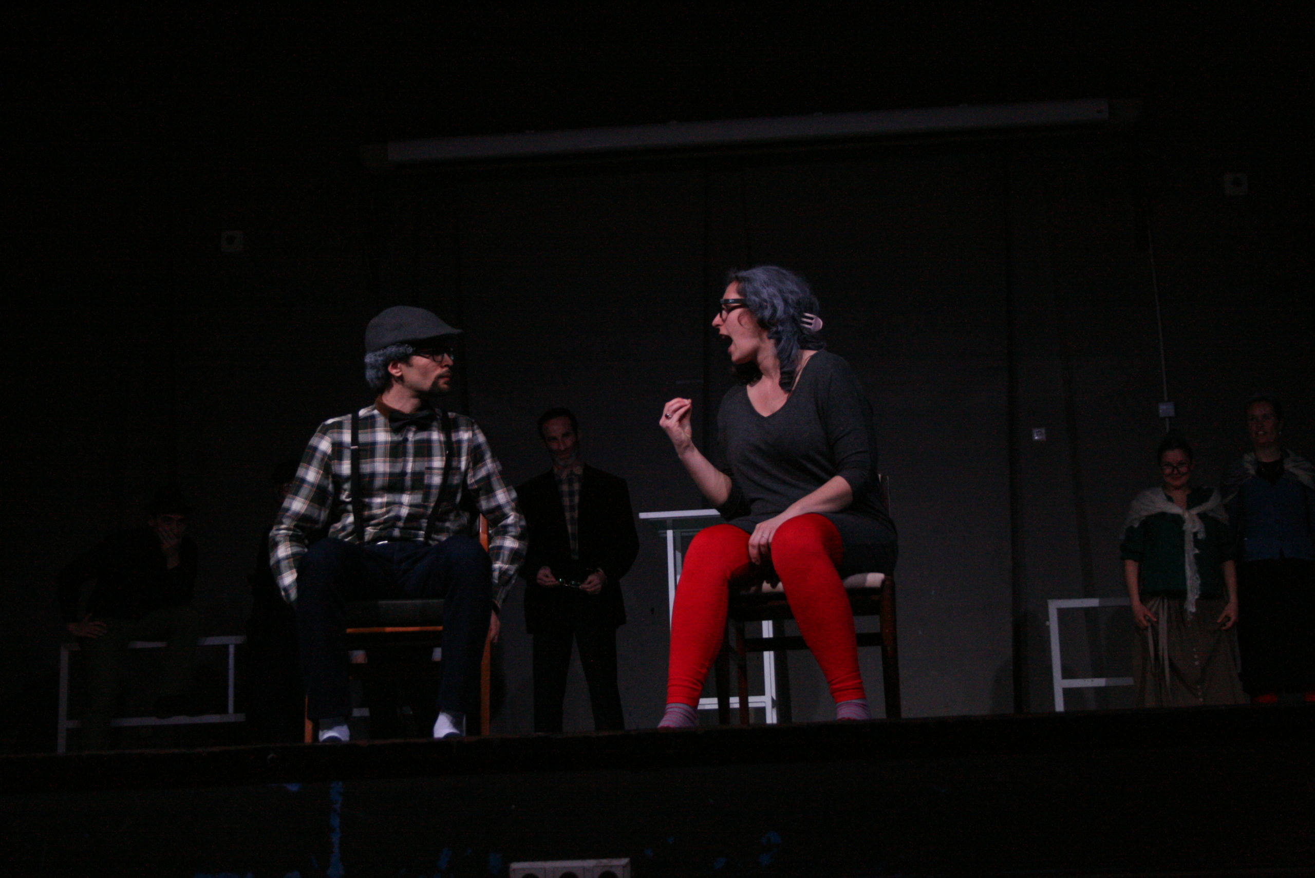 """Photo from the show """"The Chairs"""". A male and a female actor sit on chairs. The female actor yells, clearly angry, at the male actor, who listens"""