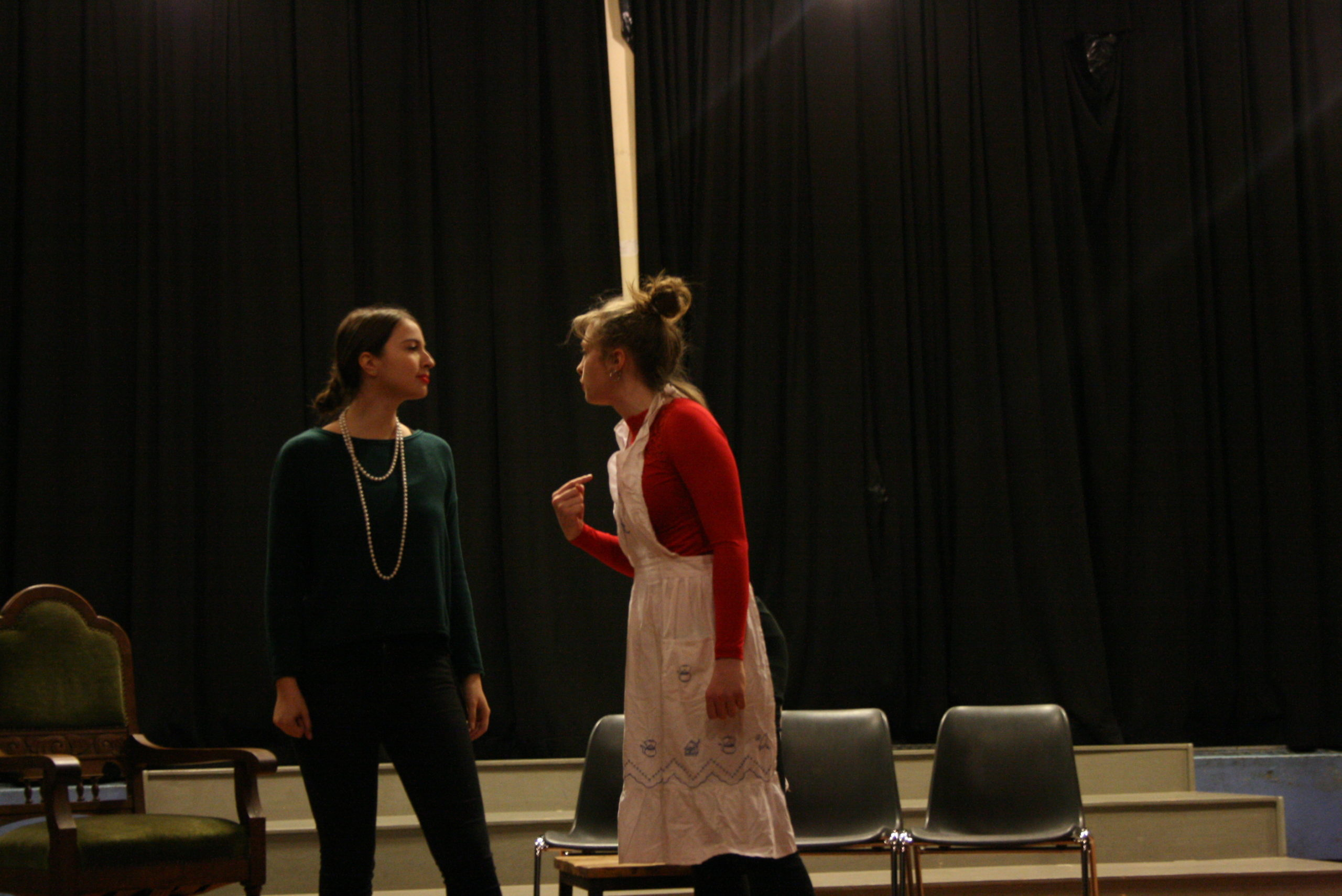 """Photo from the show """"Skin of our Teeth"""". Two female actors are on stage, one dressed like a 1920s madame, the other one like a maid. The maid points her index finger at herself, looking angrily at the madame."""