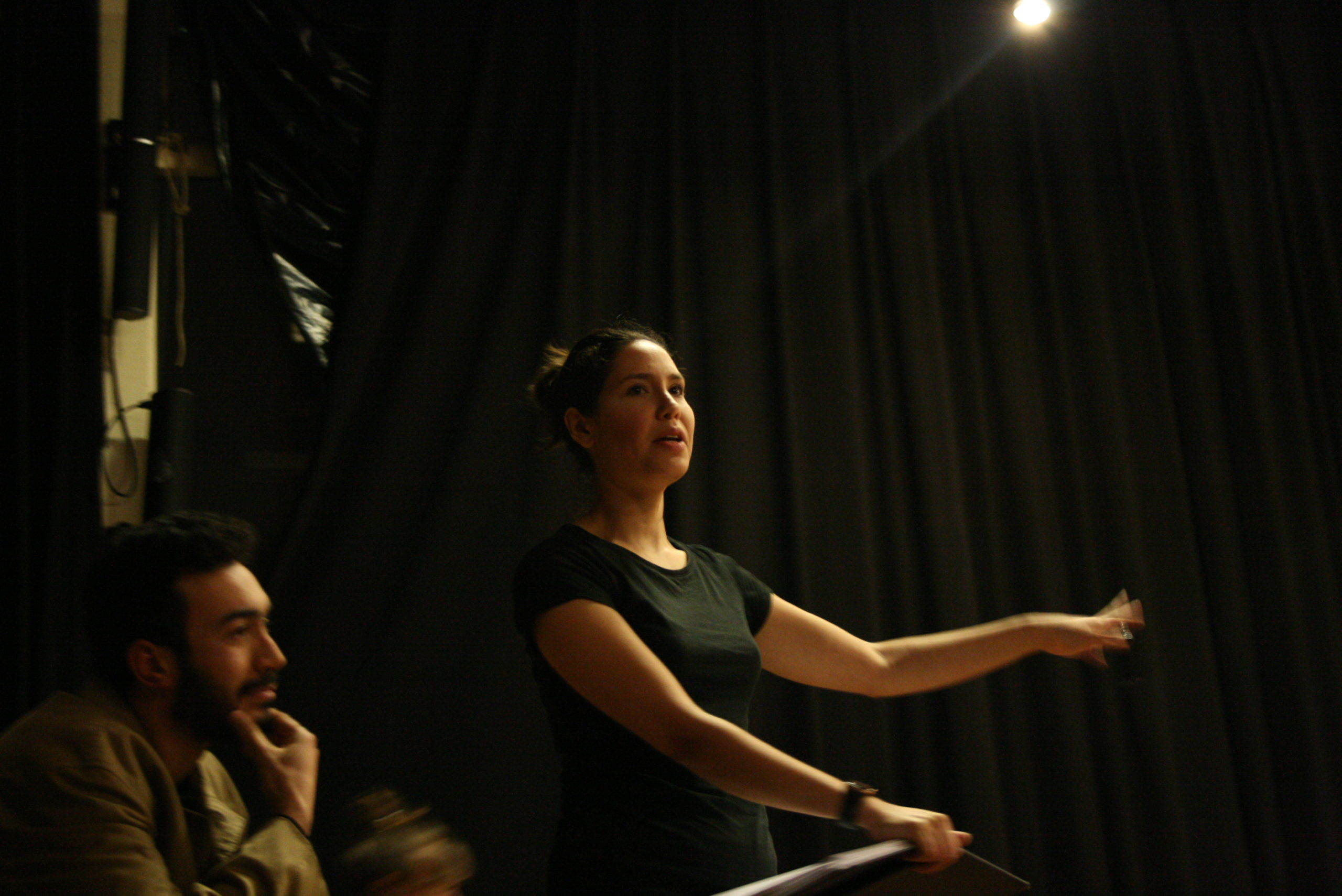 """Photo from the show """"Skin of our Teeth"""". A female actor, probably backstage, waves at someone. At the left of the photo, behind her, a man, touching his chin."""