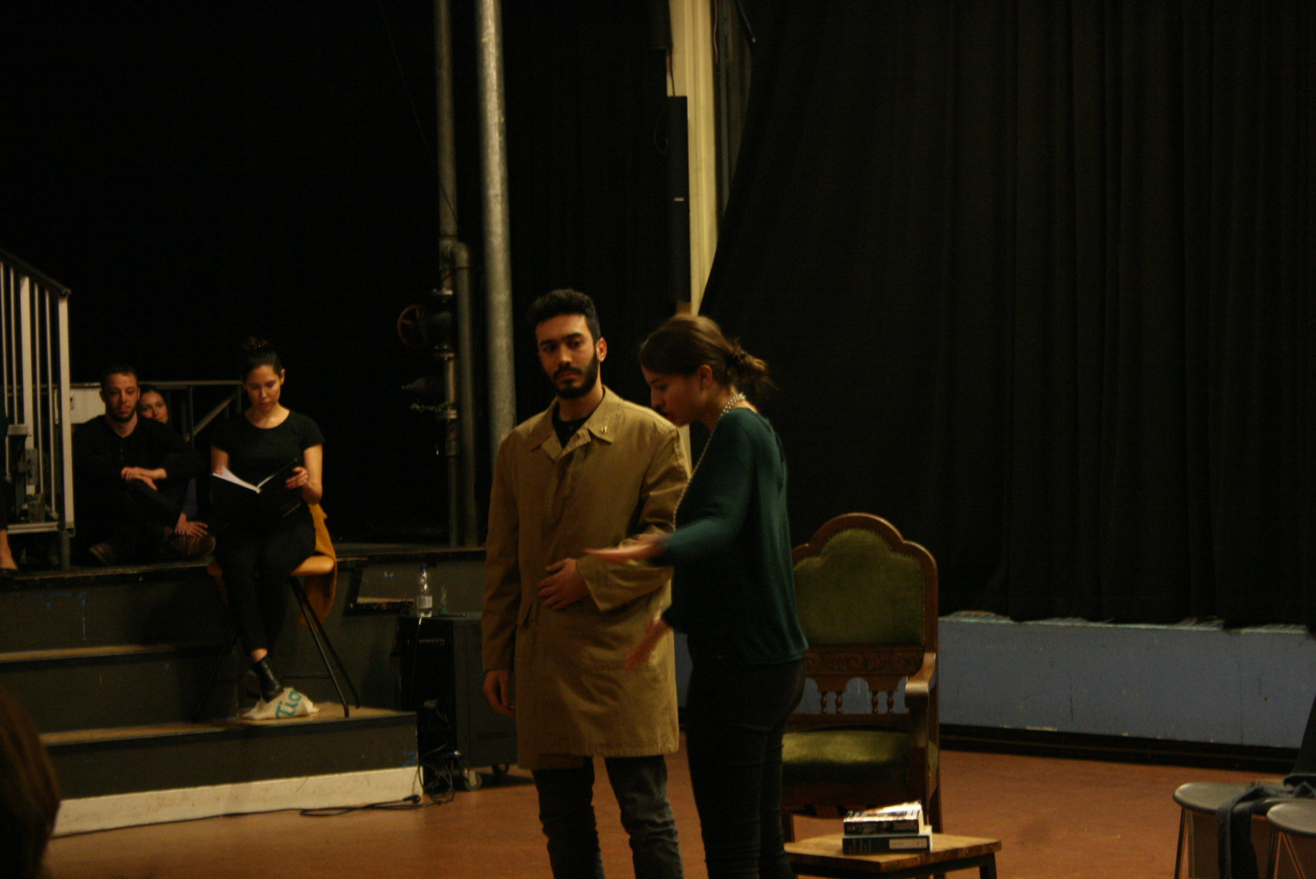 """Photo from the show """"Skin of our Teeth"""". Two actors are on stage, one dressed like a 1920s madame speaking to a man wearing a beige half-long coat"""