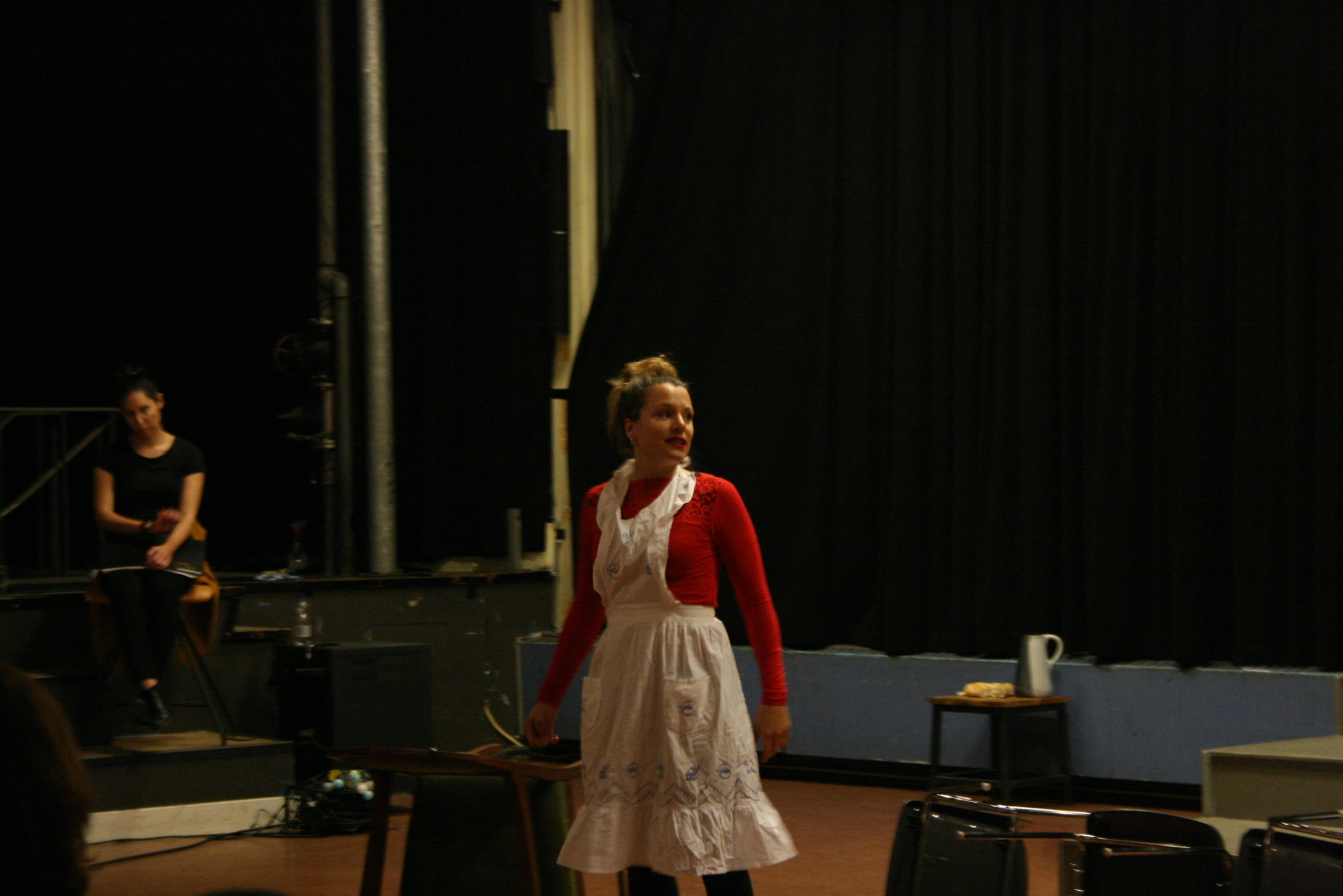 """Photo from the show """"Skin of our Teeth"""". A female actor on stage dressed as a maid, looking like she is responding to someone"""