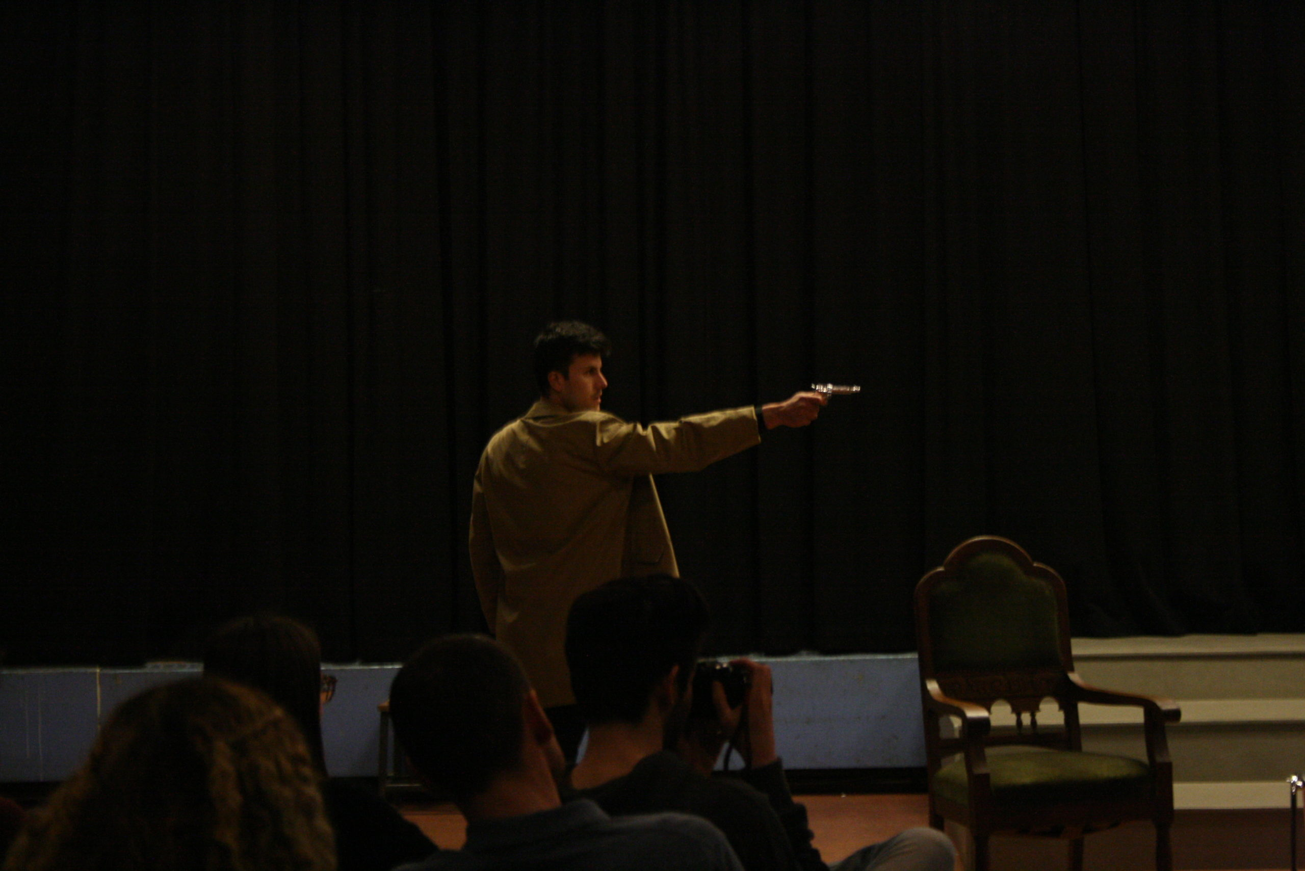 """Photo from the show """"Skin of our Teeth"""". Man with half-long beige coat is pointing the gun at someone out of the picture"""