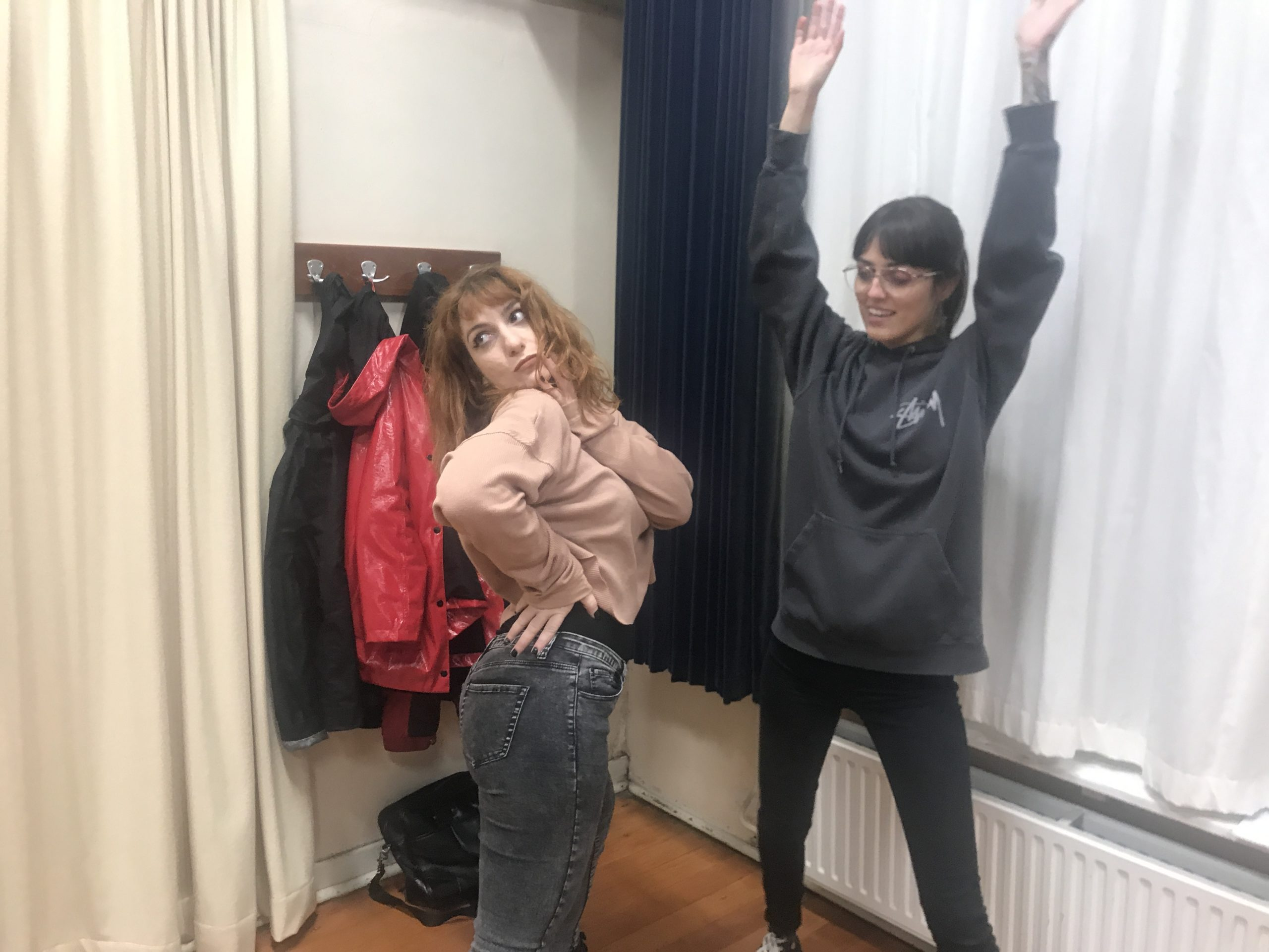 Act Attack's Improv Class. A woman pretends to look at the reflection of her back in the mirror. The other one has her arms in the air