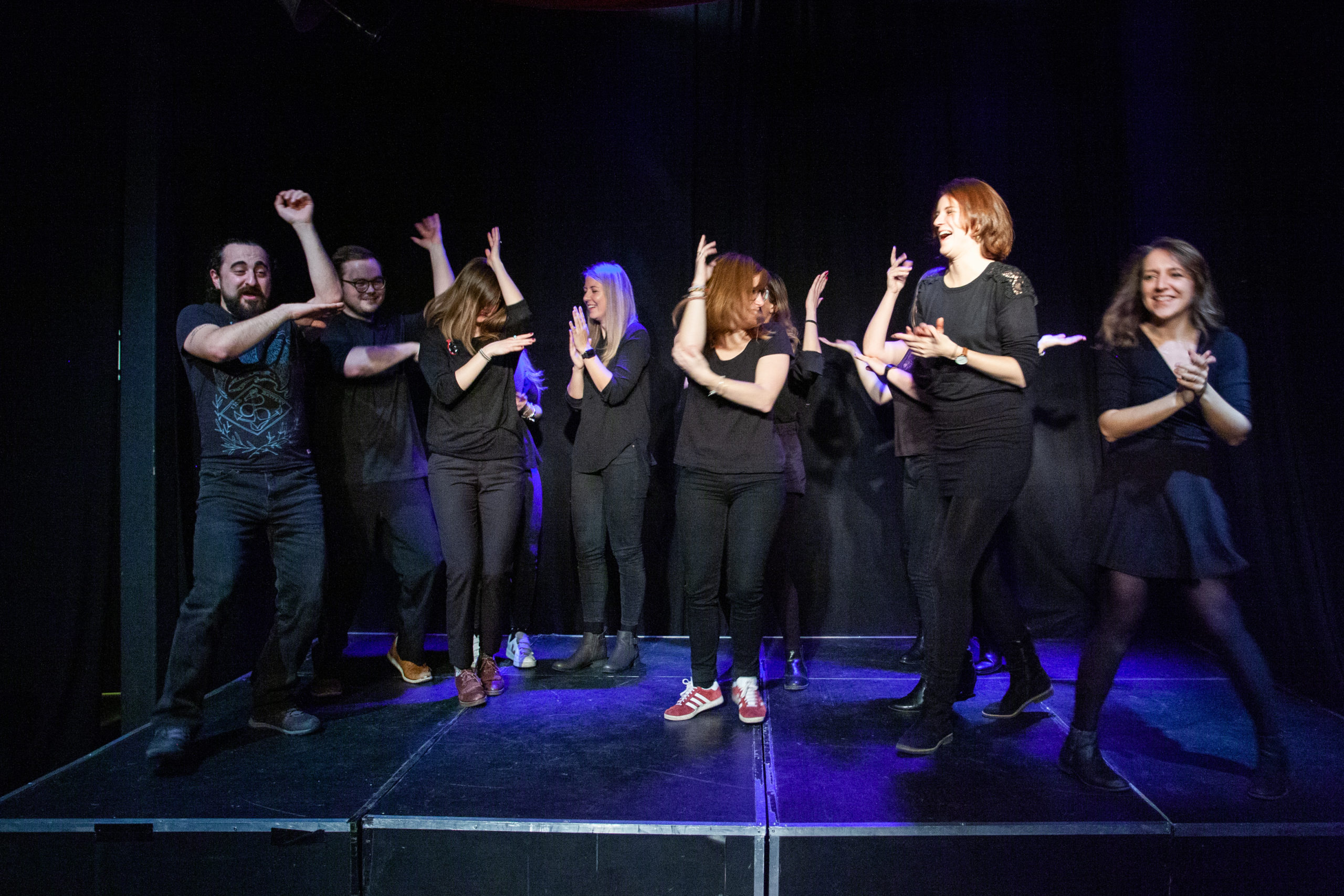 Act Attack's improv and physical show. A group of people on stage wearing black move their arms. Some have their arms placed in the shape of an L