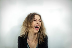 Act Attack teacher Dominika Zawada. White woman, blonde, brown eyes, black blazer. She's laughing frantically