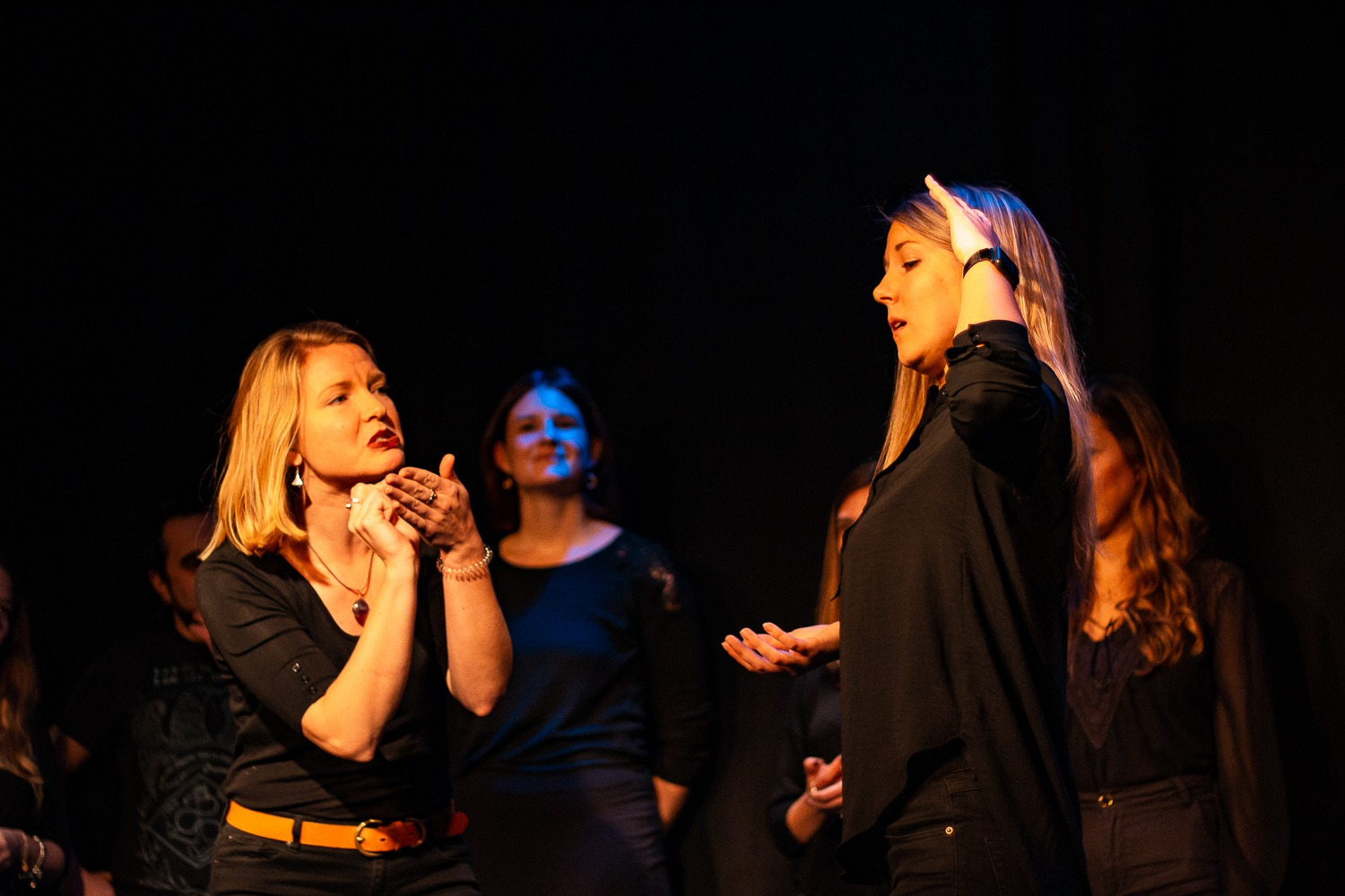Act Attack's improv and physical show. A group of people on stage wearing black. Two blonde women talking or gesturing