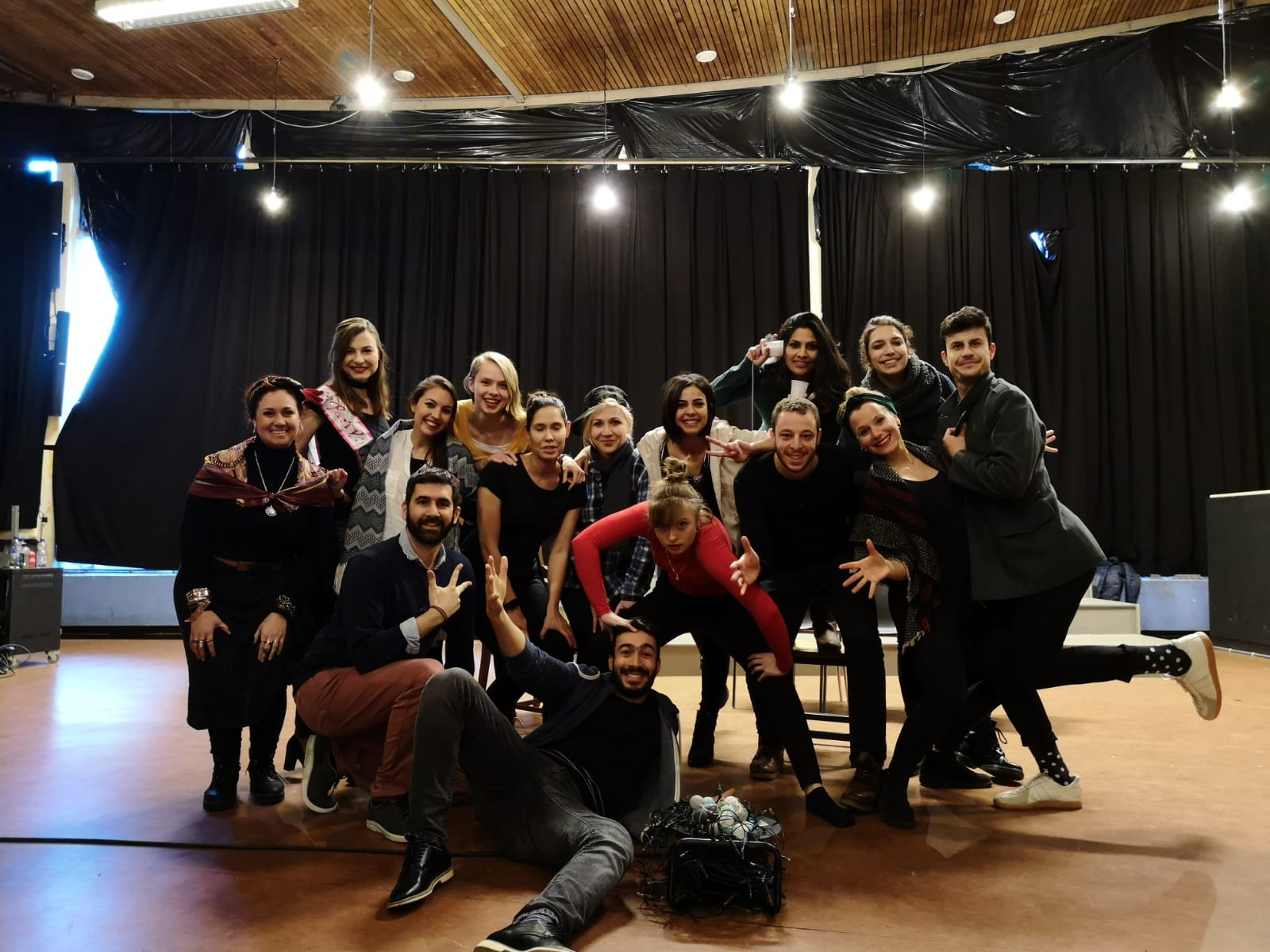 """Photo from the show """"The Skin of our Teeth"""". A group of people pose for the picture. Most of them wear black. At the back, there is a black curtain"""