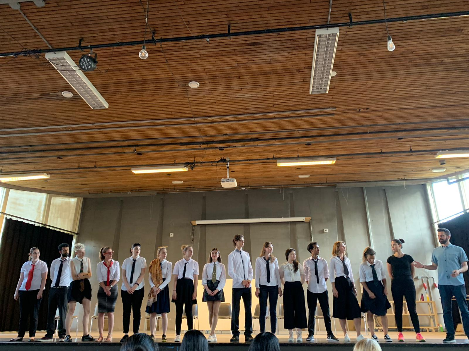 """From the show """"the magic school"""". The actors stand in a row on stage, applauding. Most of them wear a white shirt and tie"""