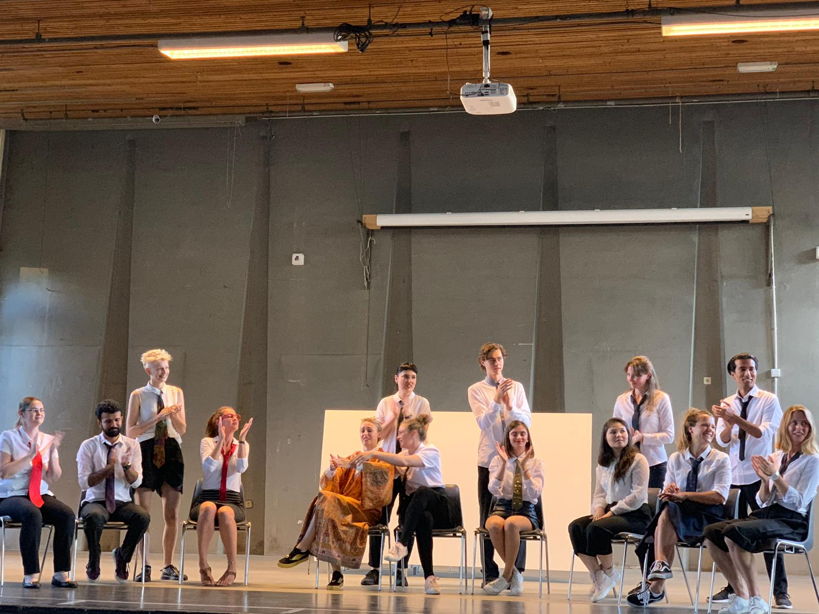 """From the show """"the magic school"""". The actors on stage are applauding. Some sit on chairs, some stand. Most of them wear a white shirt and tie"""
