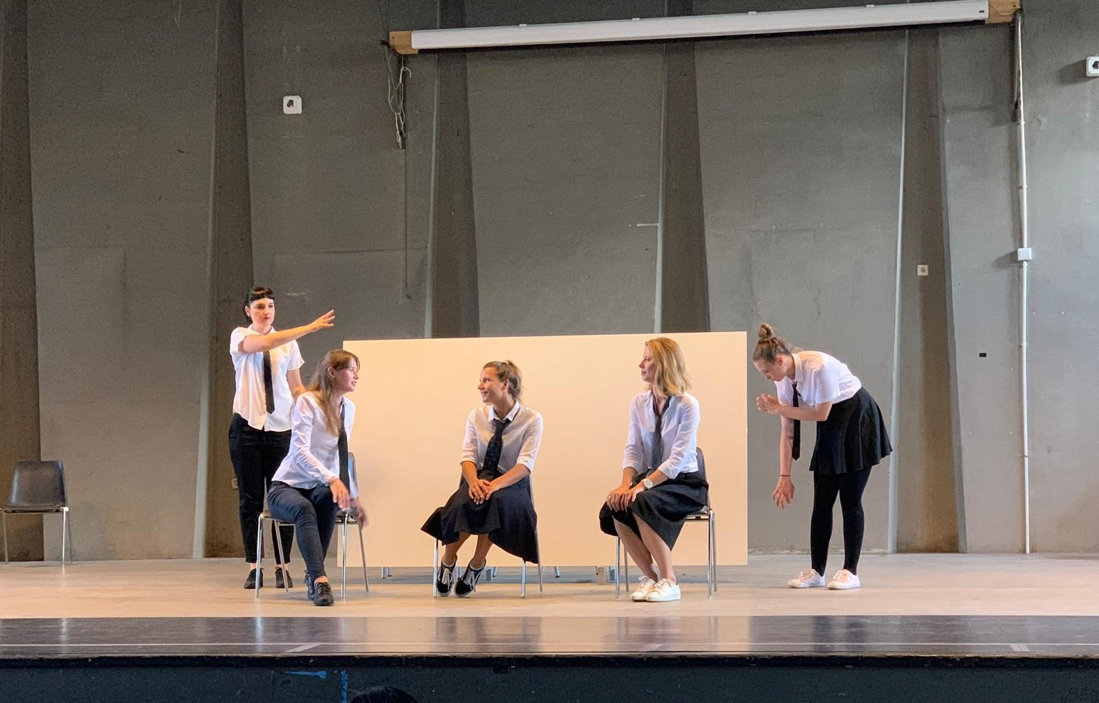 """From the show """"the magic school"""". Five actors on stage, wearing a white shirt and tie. Three are sitting, two are standing making gestures"""