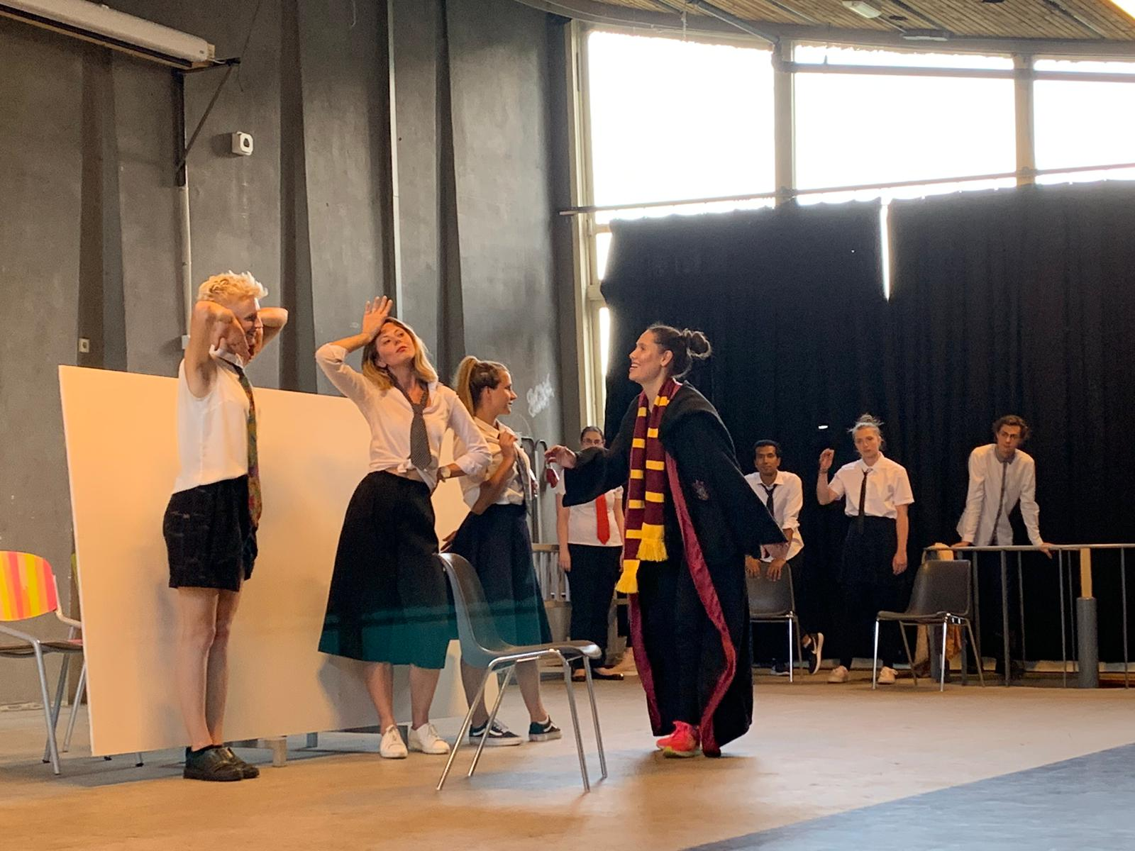 """From the show """"the magic school"""". Five actors on stage, three of them wear a white shirt and tie. The fourth one, who seems to be the teacher, approaches the students"""