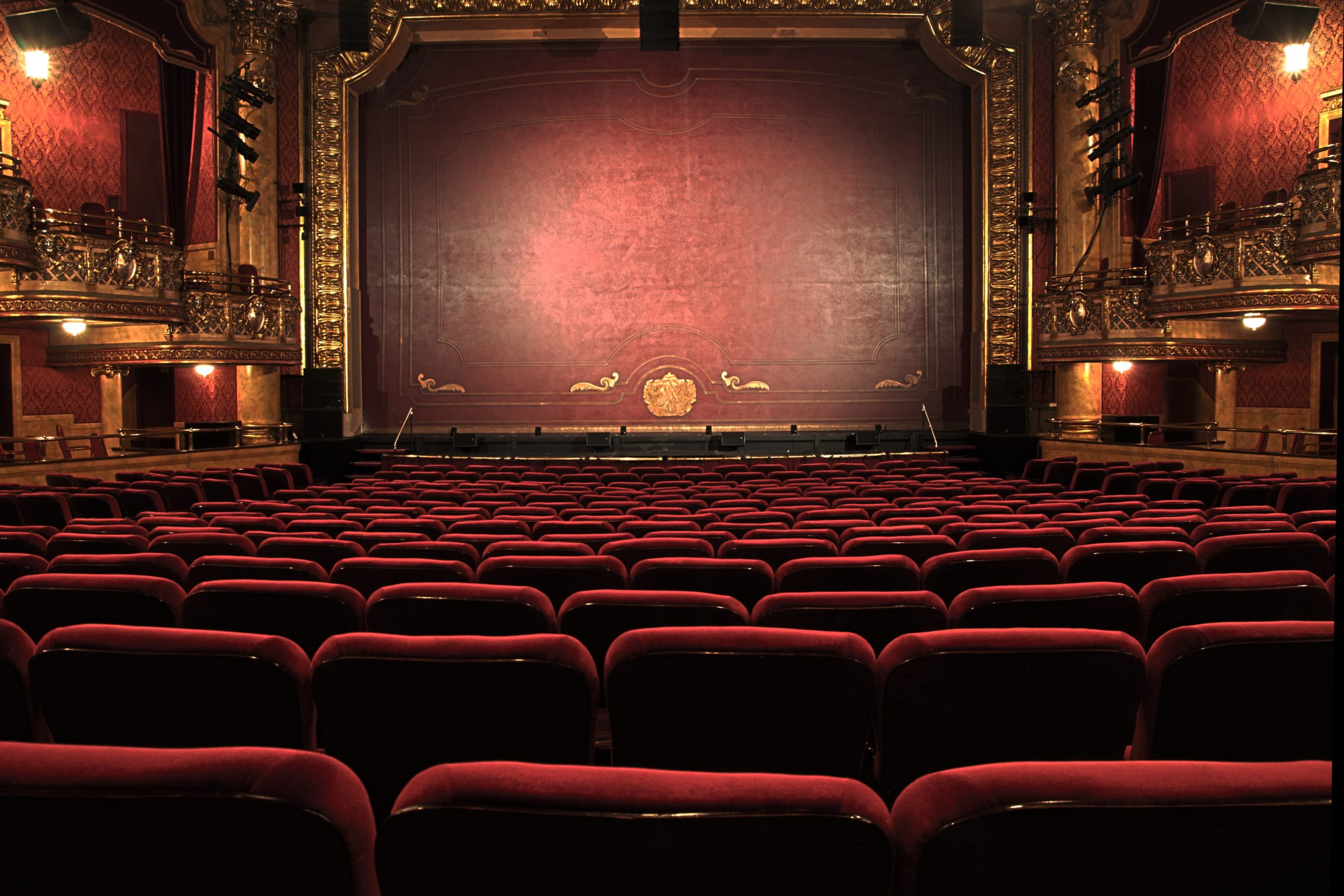 photo of an empty, old theatre. Red chairs, red walls, golden rims