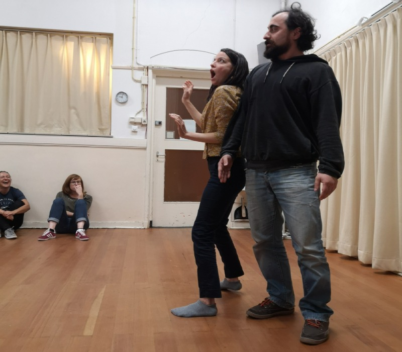 Act Attack's students from Improv and physical course practice a scene. They are both standing, shoulder to shoulder. She looks surprised and the guy looks tough.