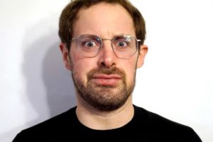 Act Attack teacher Isaac Lester Simon. Man, white, brown hair, blue eyes, beard, black top, grey metal glasses. He has a funny look, his eyes are wide open and he's blowing his lips