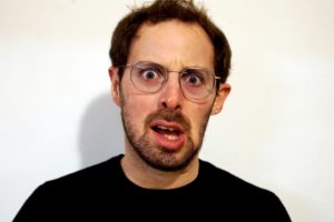 Act Attack teacher Isaac Lester Simon. Man, white, brown hair, blue eyes, beard, black top, grey metal glasses. He looks shocked but in a funny way, his lower lip drops to the side