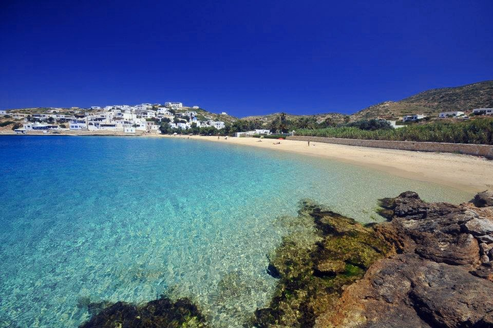 A beautiful beach located in the Greek island of Donoussa. Crystal clear water, golden sand. At its back, a typical Greek village with white houses and mountains.
