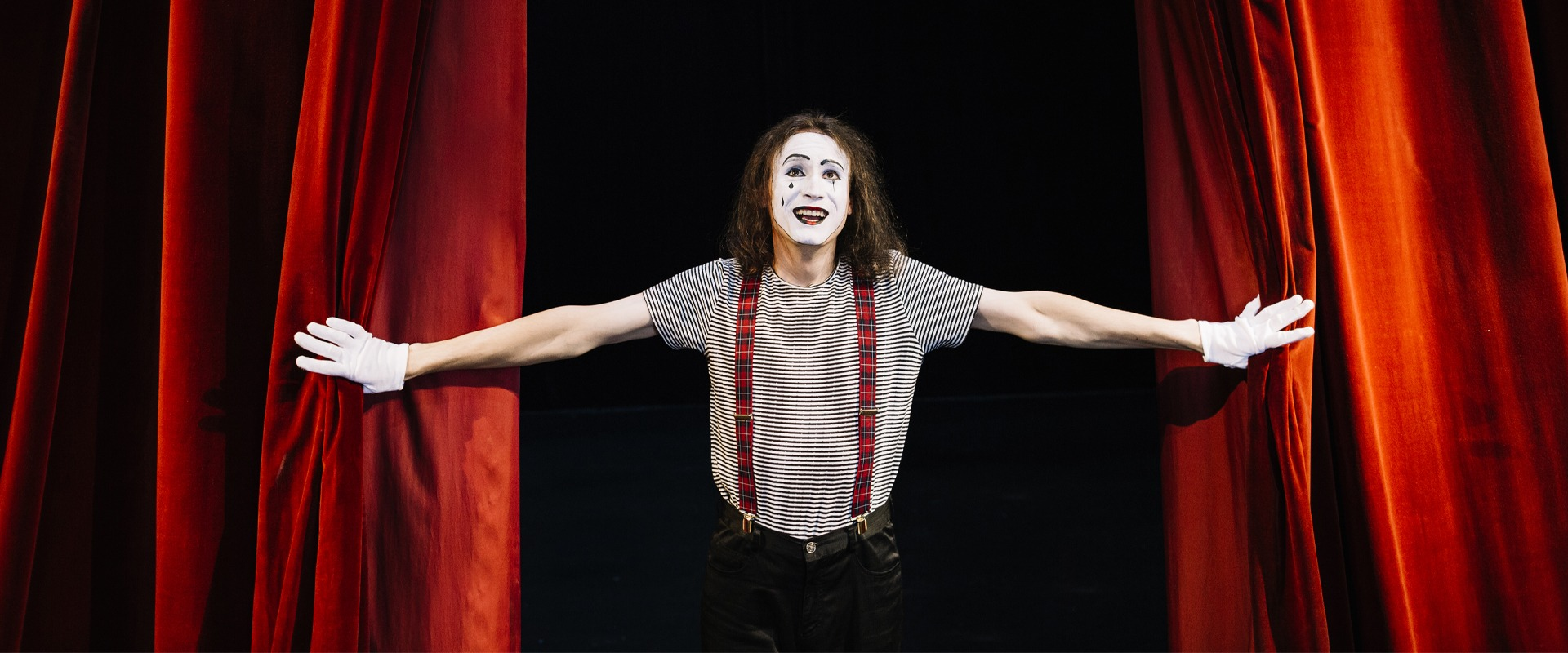 Actor masked as Pierrot open the red curtains and enters the stage