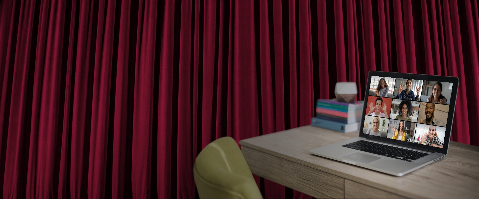 Red theater curtains, a green chair , a desk and a laptop with nine people on screen